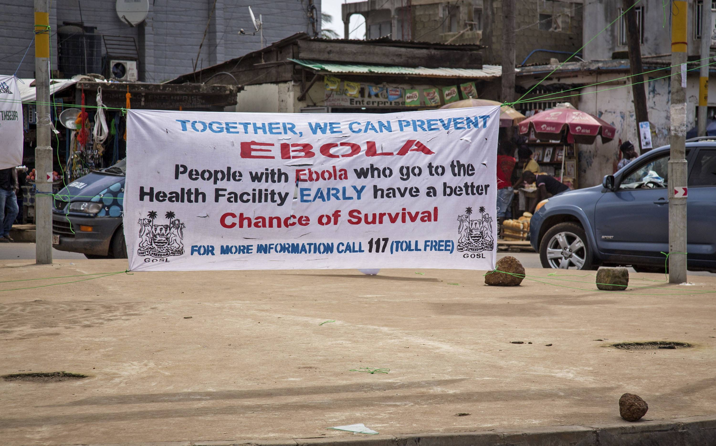 A banner encouraging people suffering from Ebola to go immediately to a health center for treatment on a sidewalk in the city of  Freetown, Sierra Leone.
