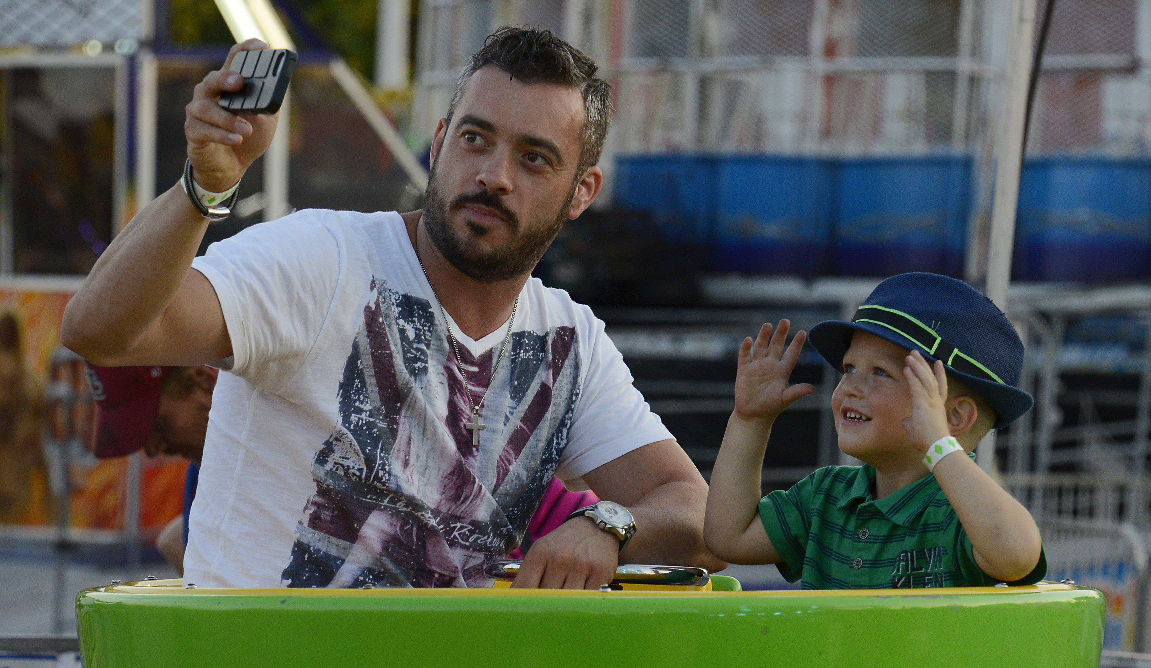 Catalin Colcer, 3, and Alex Sorescu of Joliet enjoy the teacup ride while taking a selfie Thursday at St. Zachary Church's Augustfest in Des Plaines.