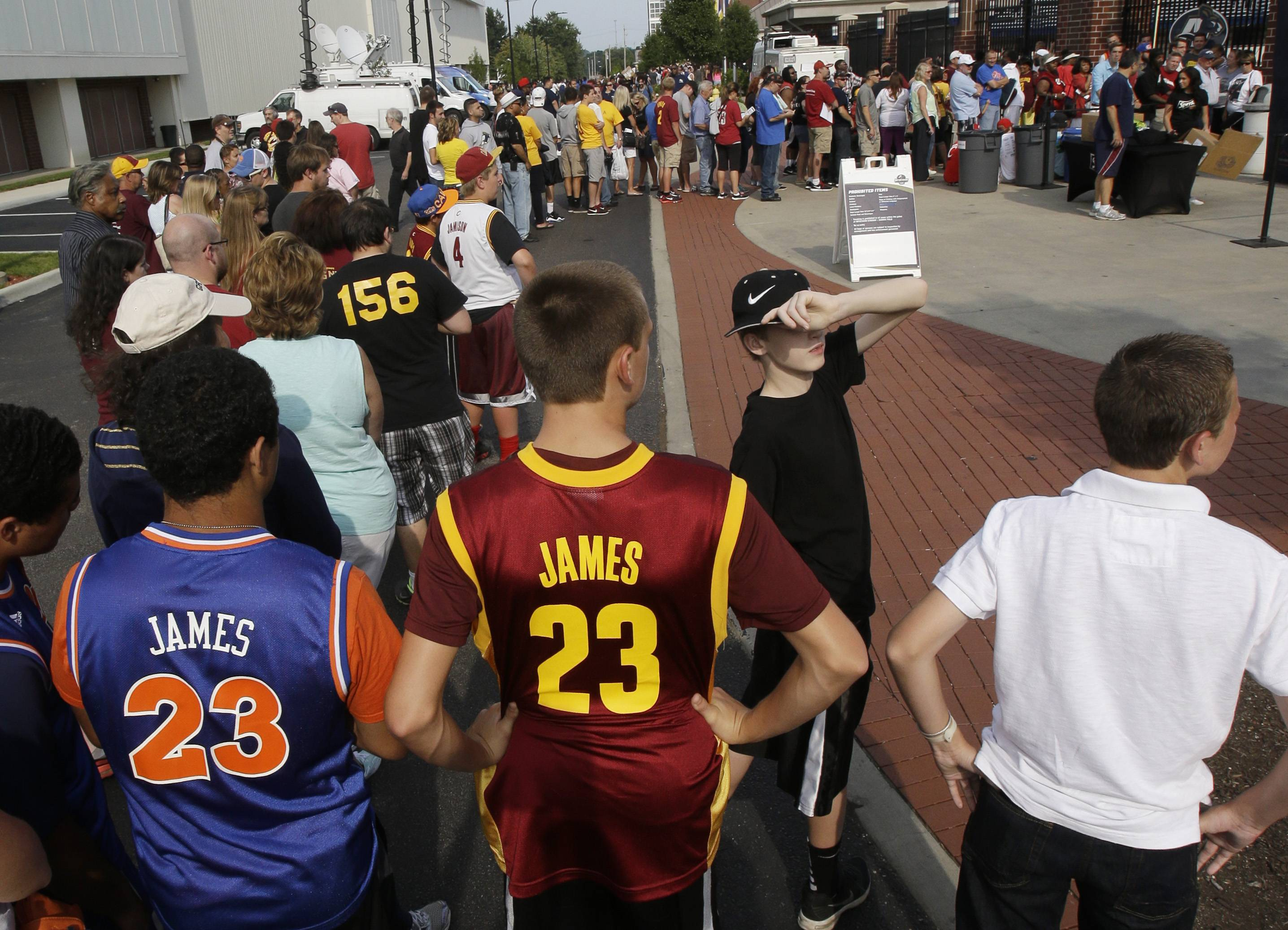 From left to right, Bryce Traylor and Corey Oswald, both 14, wait in line to enter InfoCision Stadium for the LeBron James homecoming Friday, Aug. 8, 2014, in Akron, Ohio. James is being welcomed back Friday night by the city where he first bounced a basketball. James grew up in Akron and has maintained a strong connection with his hometown.