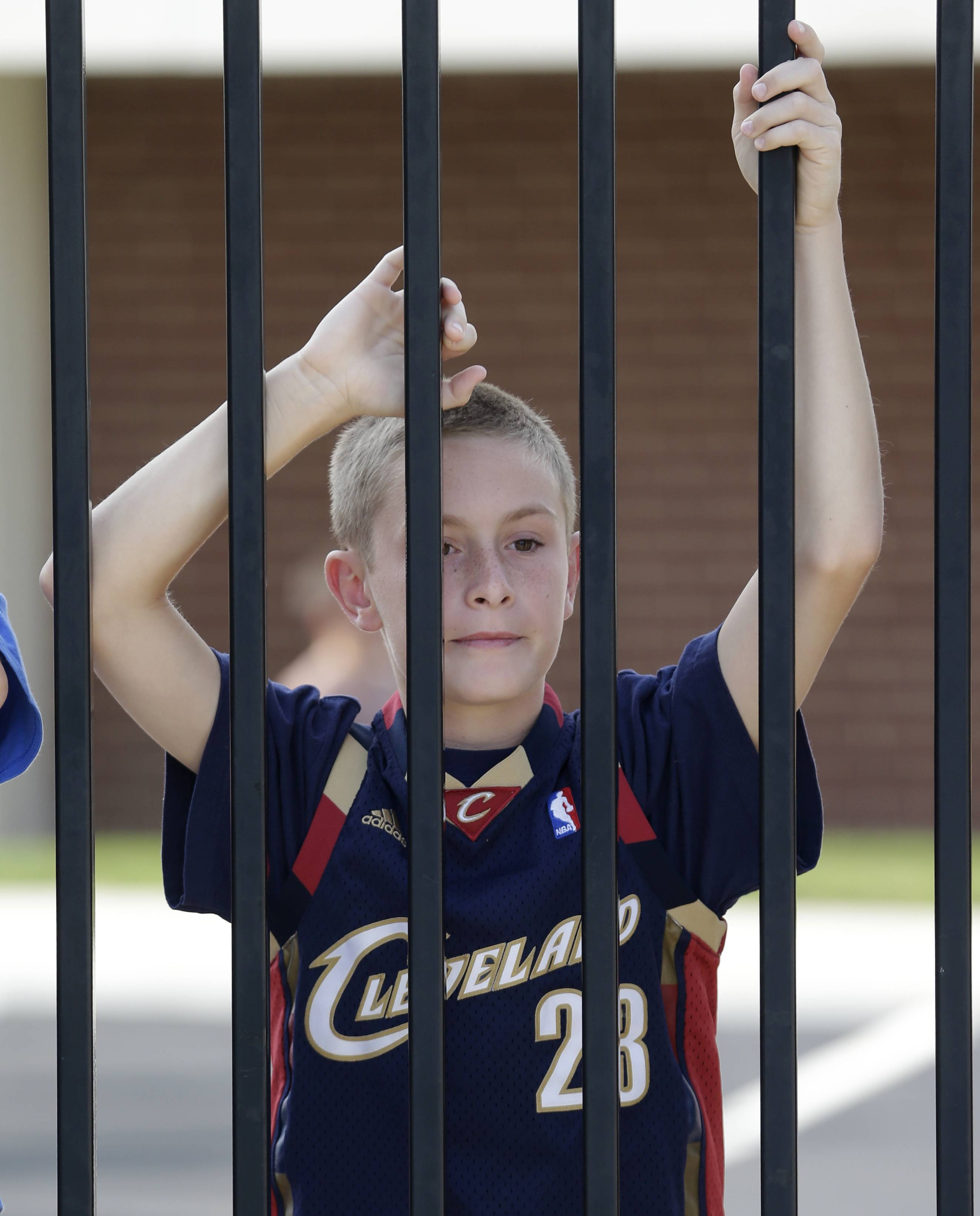 Kolten Kurtz, 11, looks into the stadium before the LeBron James homecoming Friday, Aug. 8, 2014, in Akron, Ohio. James is being welcomed back Friday night by the city where he first bounced a basketball. The NBA superstar is being celebrated with an event expected to draw more than 25,000 people to InfoCision Stadium. James grew up in Akron and has maintained a strong connection with his hometown.