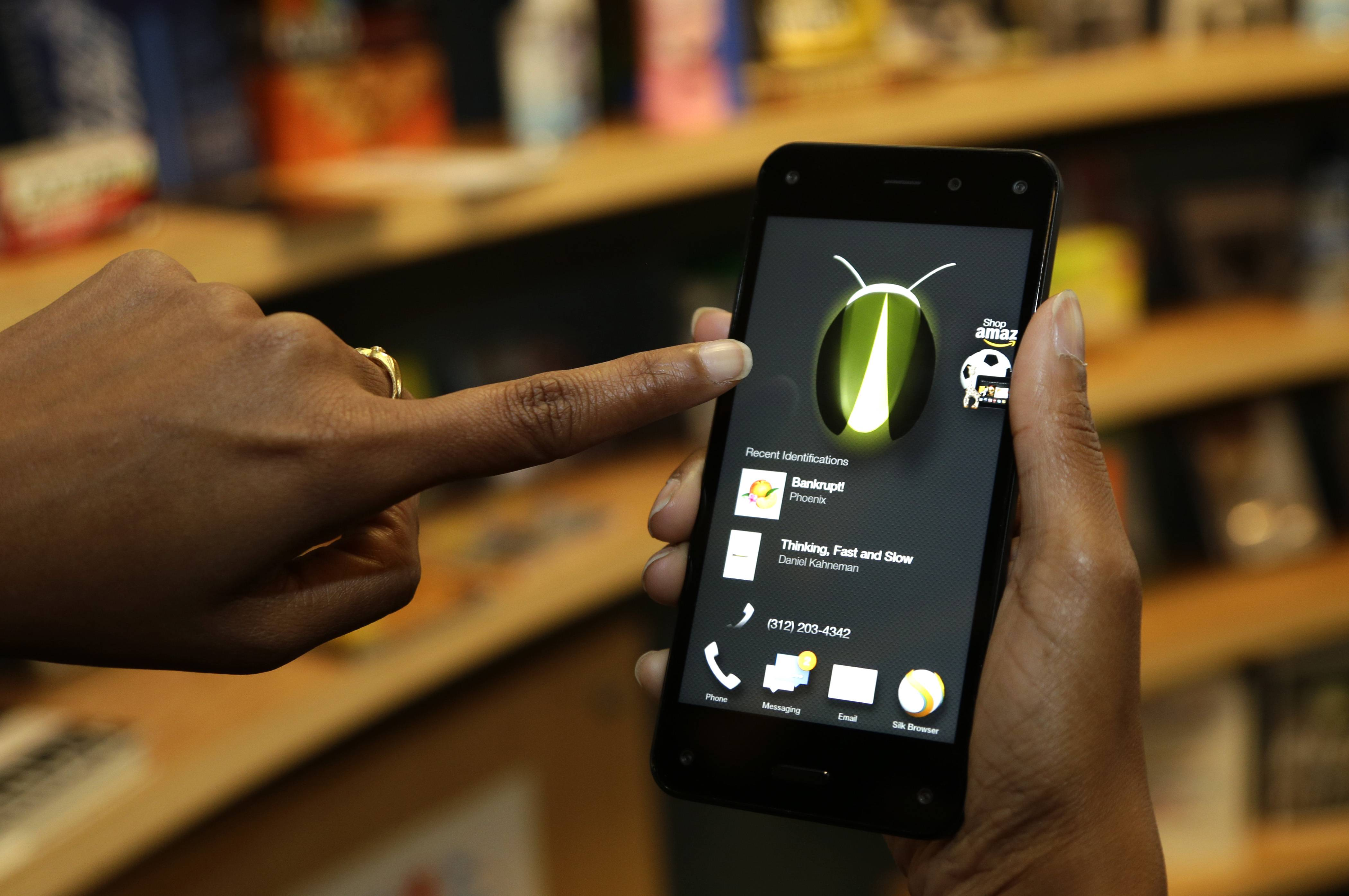 The new Amazon Fire Phone's Firefly feature, which lets the user take a photo of objects, numbers, artwork or books and have the phone recognize the item, is demonstrated in Seattle. Firefly also can recognize songs, TV shows, and movies.