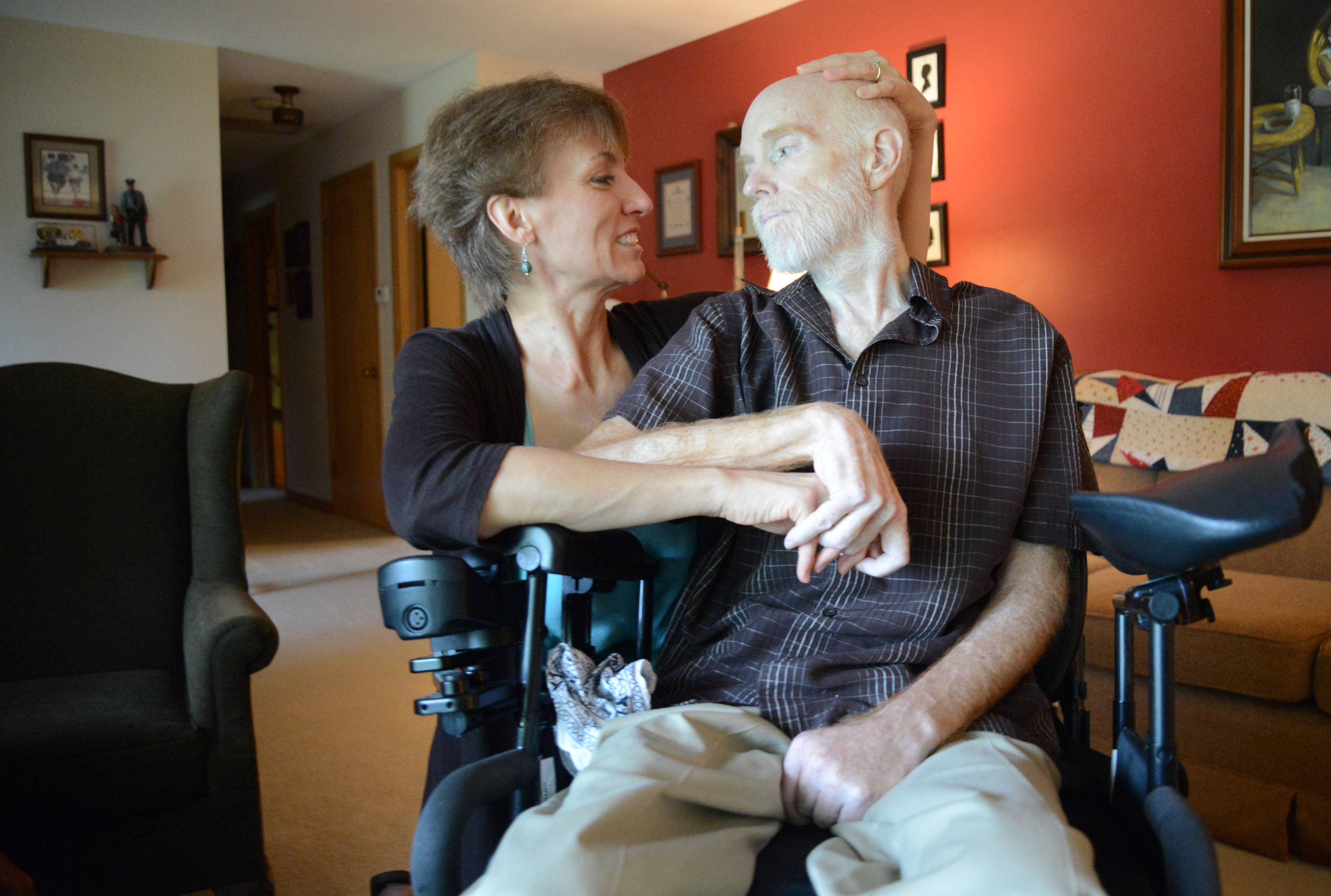 Dawn Linder comforts her husband, Tom Linder, a retired police officer, in their Elgin home. He suffered a stroke three months after retiring in February 2012.
