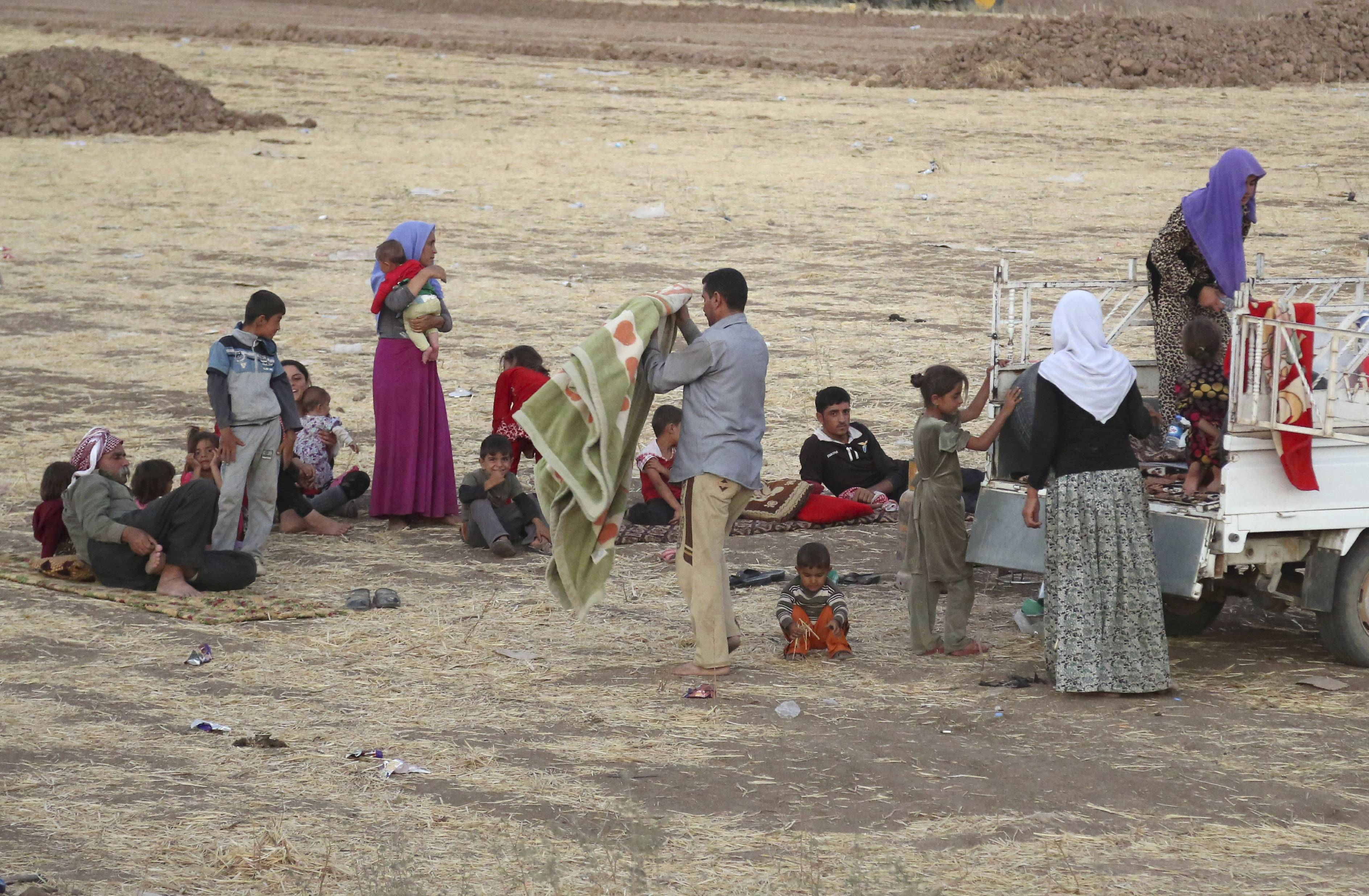 Displaced Iraqis from the Yazidi community settle Saturday outside the camp of Bajid Kandala at Feeshkhabour town near the Syria-Iraq border.
