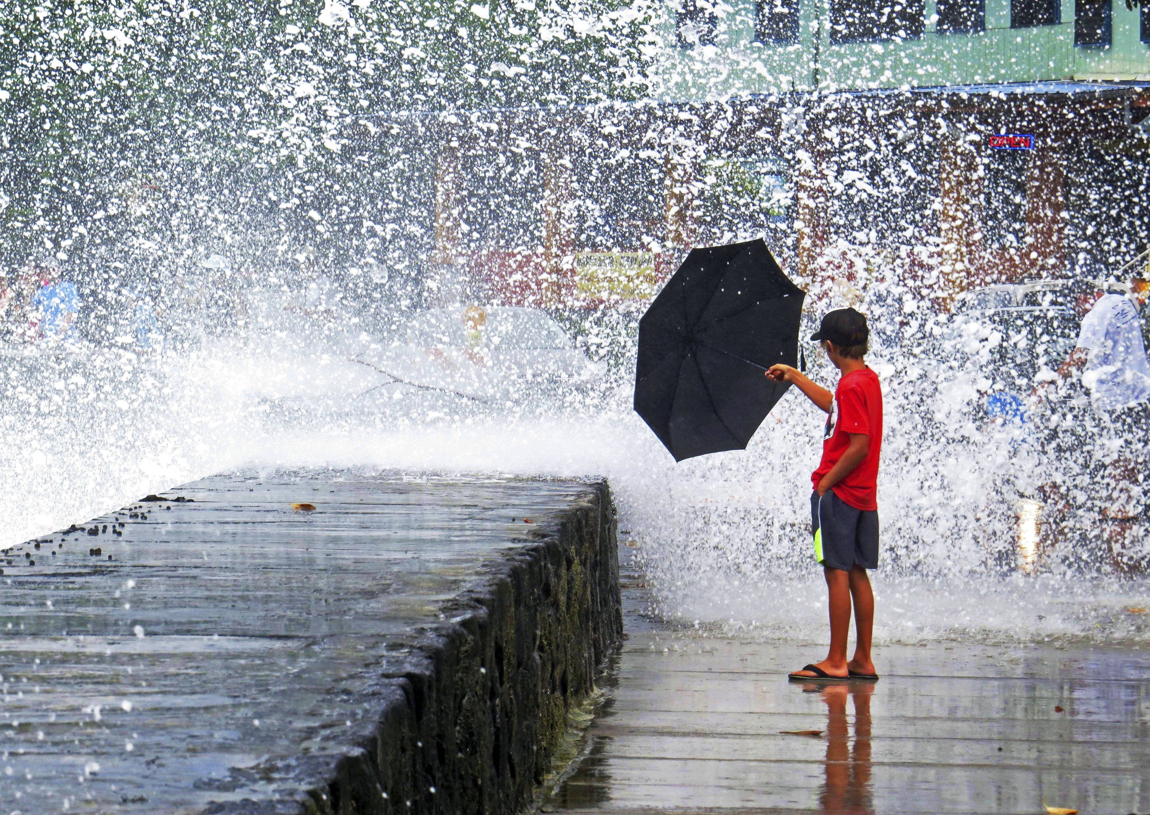 A boy holds an umbrella to a wave Friday in Kailua-Kona on the island of Hawaii.