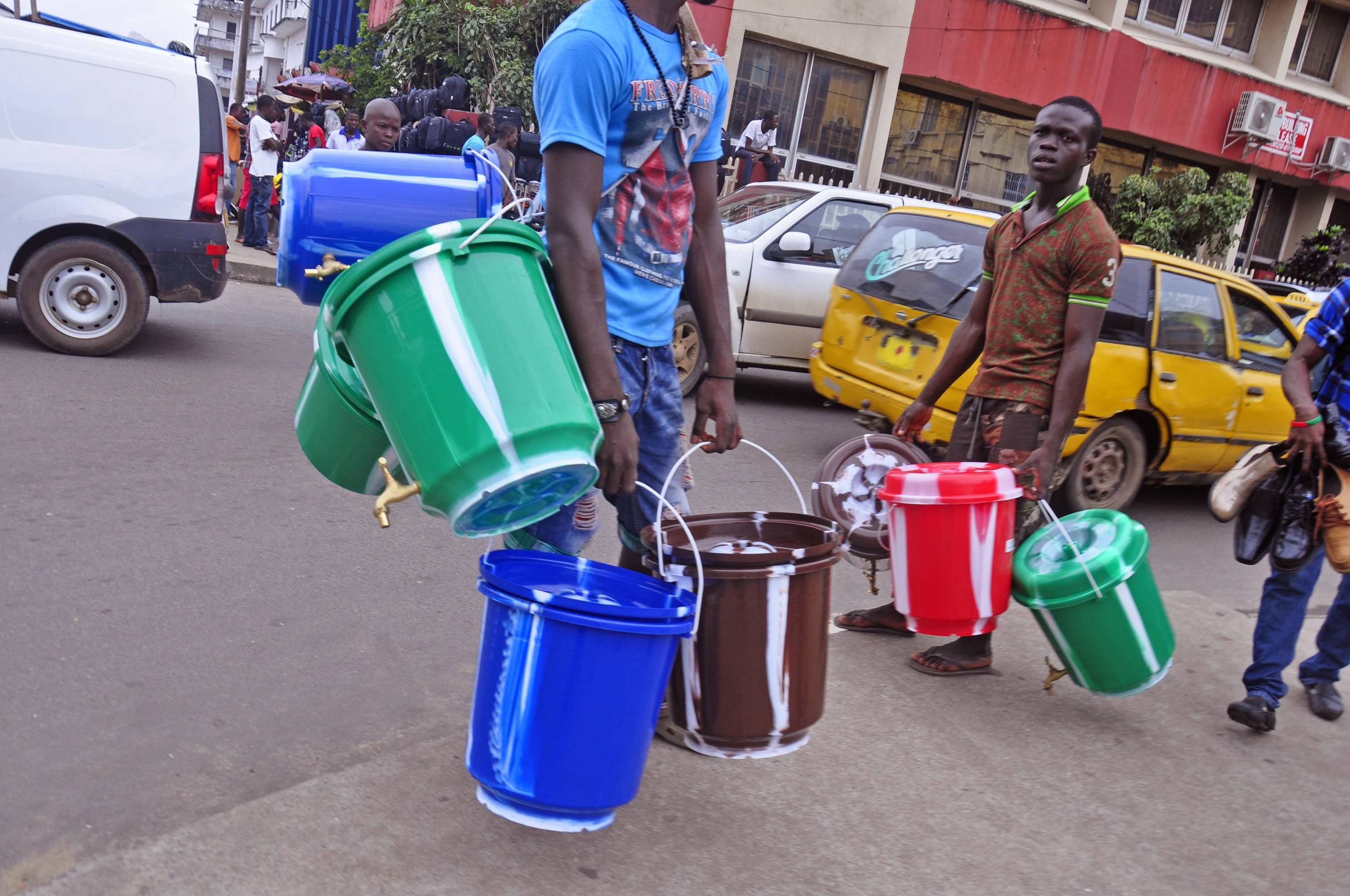 Water bucket sellers hawk their wares Wednesday as the public buys them to try to protect themselves from the deadly Ebola virus, in Monrovia, Liberia. The price of buckets has increased as Liberian people are encouraged to wash their hands after filling it with disinfectant to prevent the spread of the deadly Ebola virus. The World Health Organization has declared the outbreak an international emergency.
