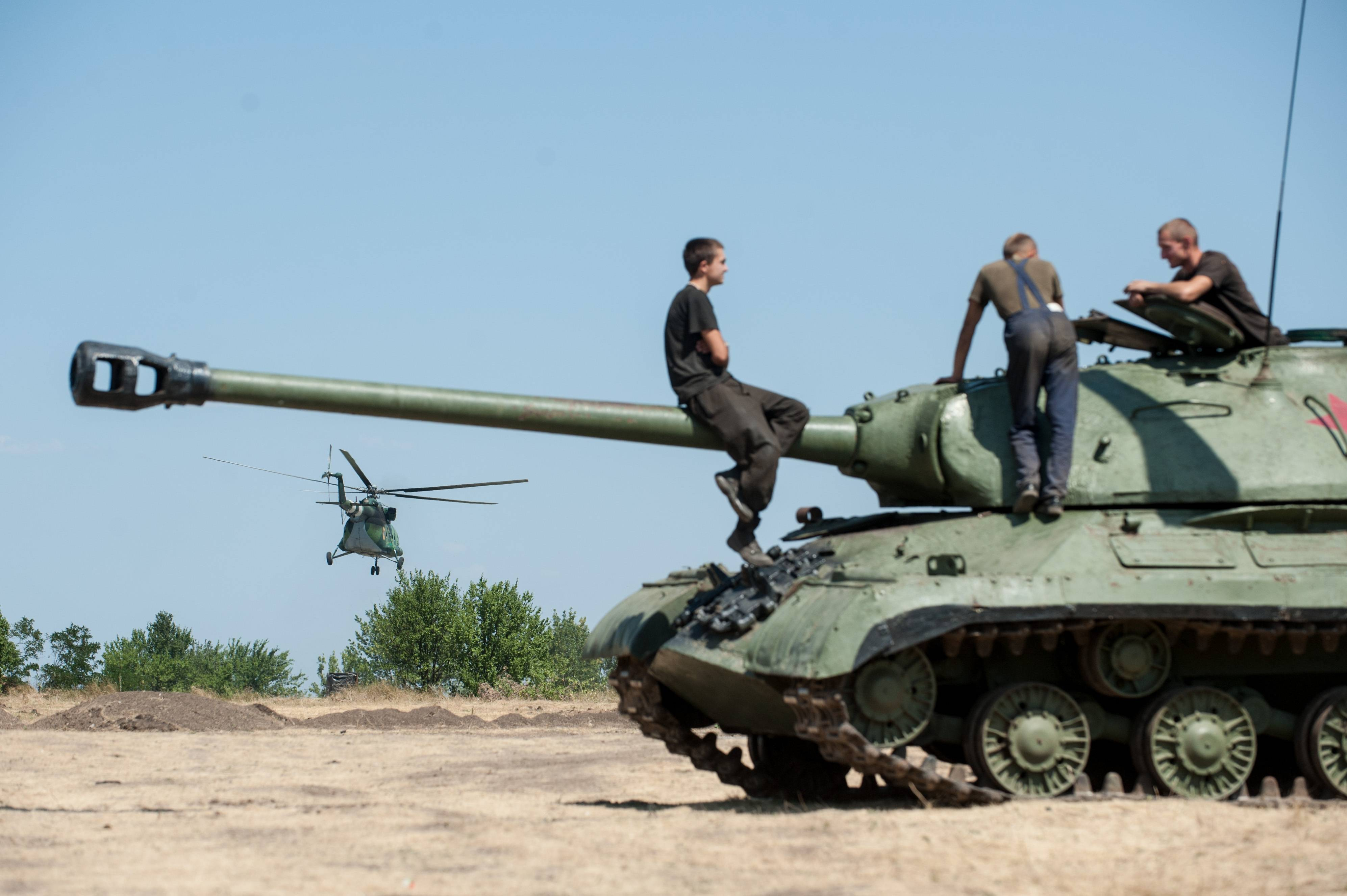 Ukrainian government soldiers sit atop of a tank in Donetsk region, eastern Ukraine, Saturday, Aug. 9, 2014. A top commander of the pro-Russia insurgency in eastern Ukraine said Saturday that Ukrainian forces have seized a key town, leaving the rebel region's largest city of Donetsk surrounded.