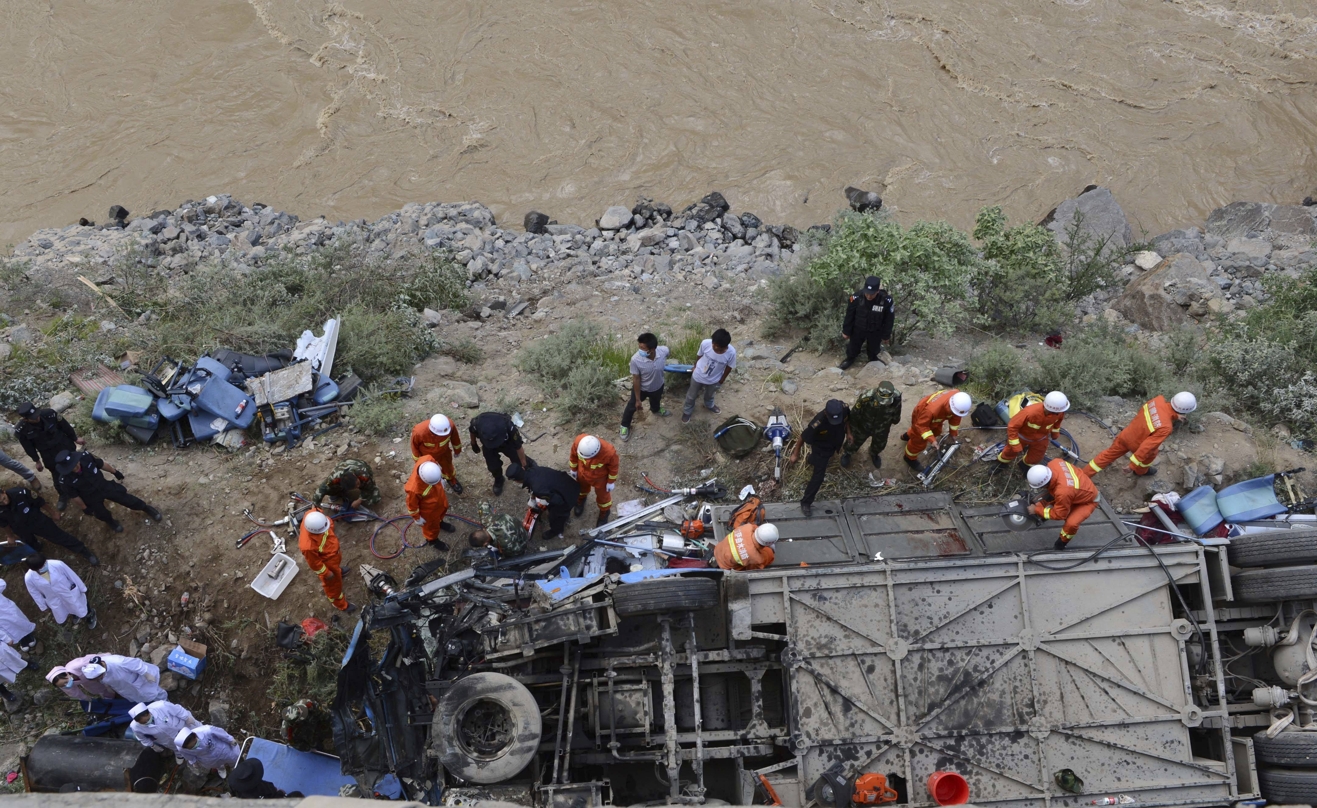 In this photo released by China's Xinhua News Agency, rescuers work around an overturned tour bus after it fell off a 10-meter (30-foot) cliff in Nyemo County, southwest China's mountainous region of Tibet Saturday, Aug. 9, 2014. Xinhua reported the bus carrying about 40 people careened after it crashed in a pileup involving a sports utility vehicle and a pickup truck on a state road. Casualty details were not immediately known.