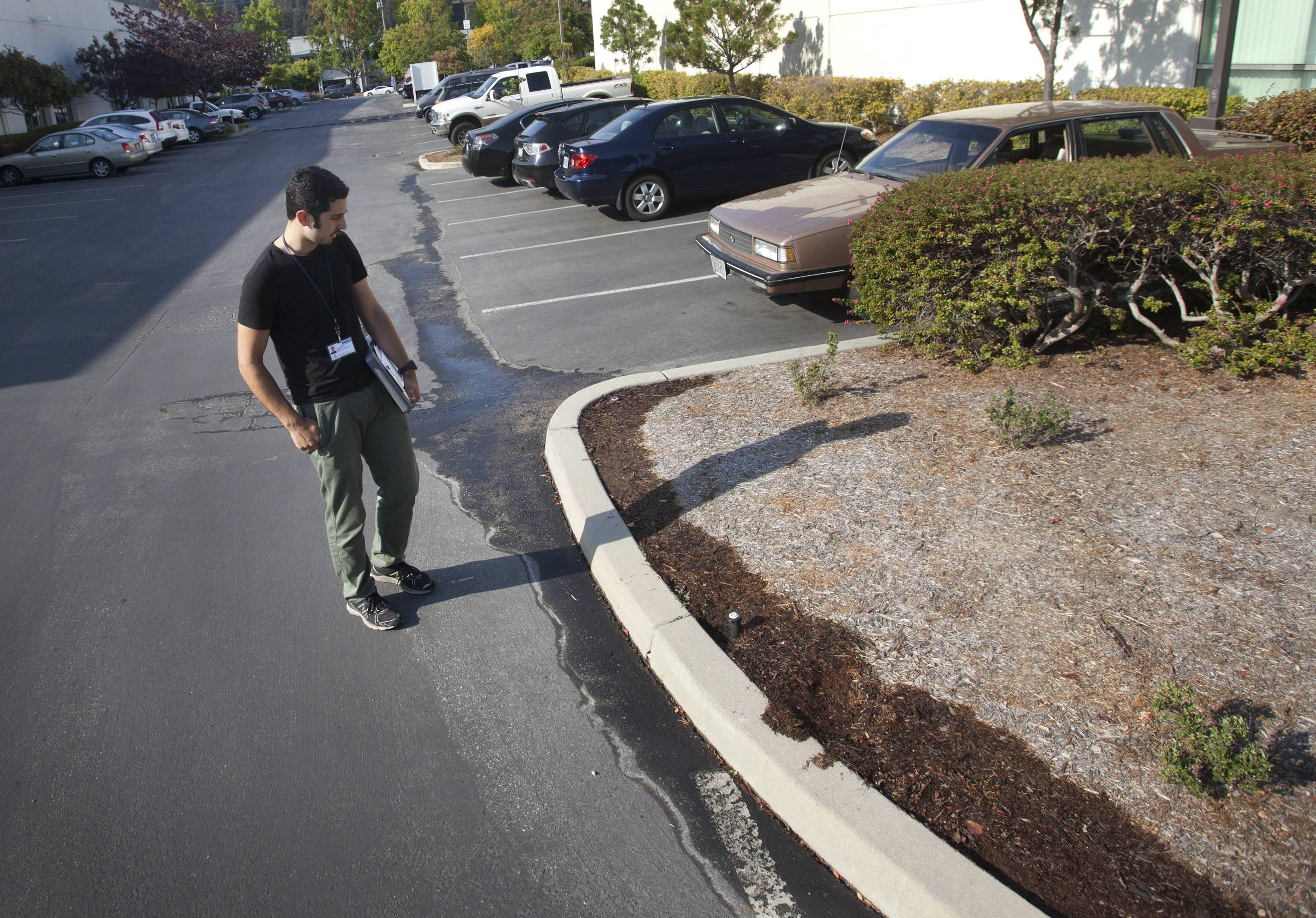Nik Martinelli, a water conservation specialist for the city of Santa Cruz, looks at water run-off from a plant irrigation system at an office park in Santa Cruz, Calif., Tuesday, July 29, 2014. Unlike most cities that have either groundwater, a connection to state water canals, or vast reservoirs, Santa Cruz is among those worst hit by the drought because it relies almost exclusively on storm runoff into a river, some creeks and an aging reservoir.