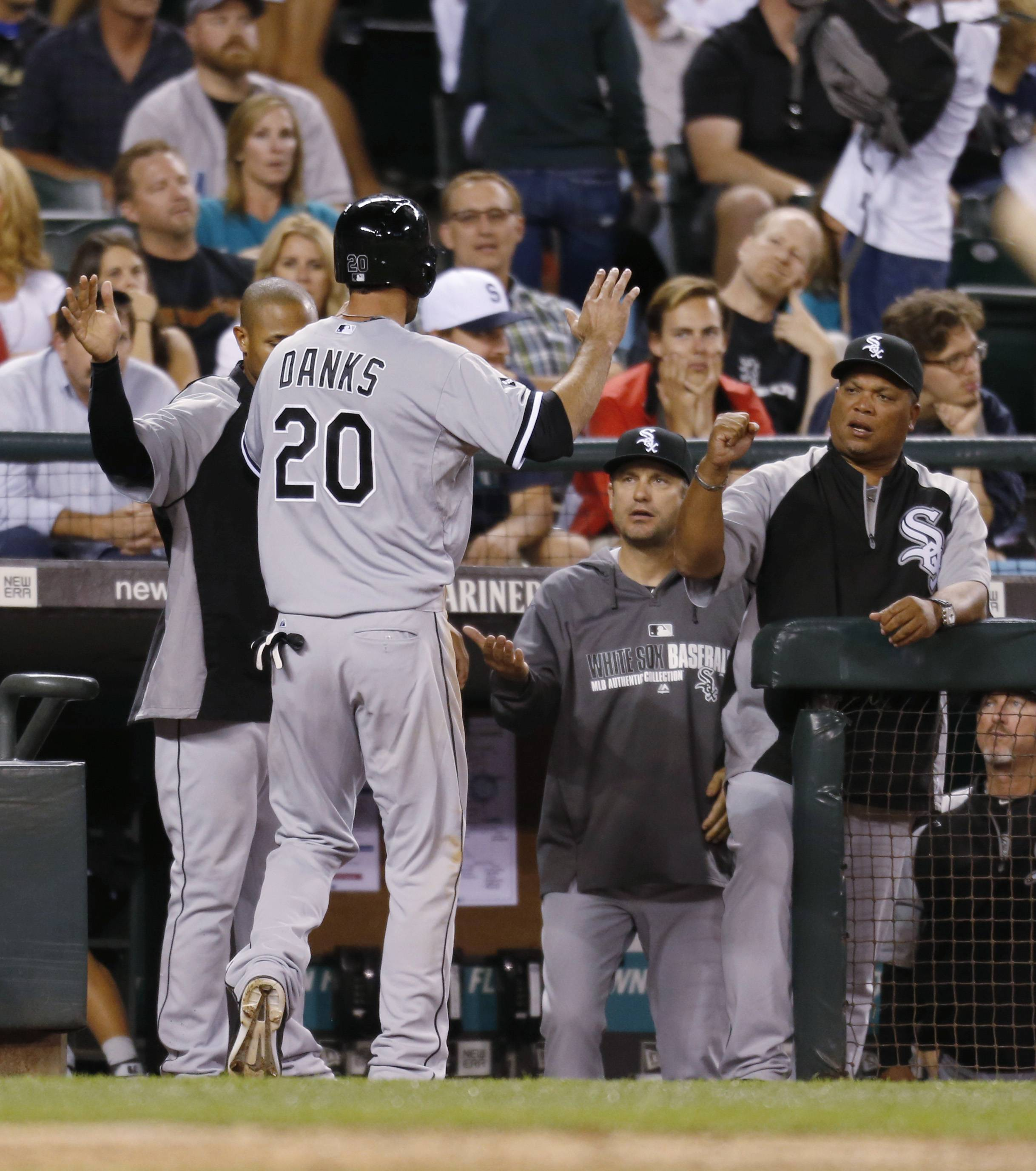 The White Sox's Jordan Danks is greeted at the dugout after scoring against the Seattle Mariners during the 10th inning of a baseball game in Seattle on Saturday, Aug. 9, 2014. The White Sox won 2-1.