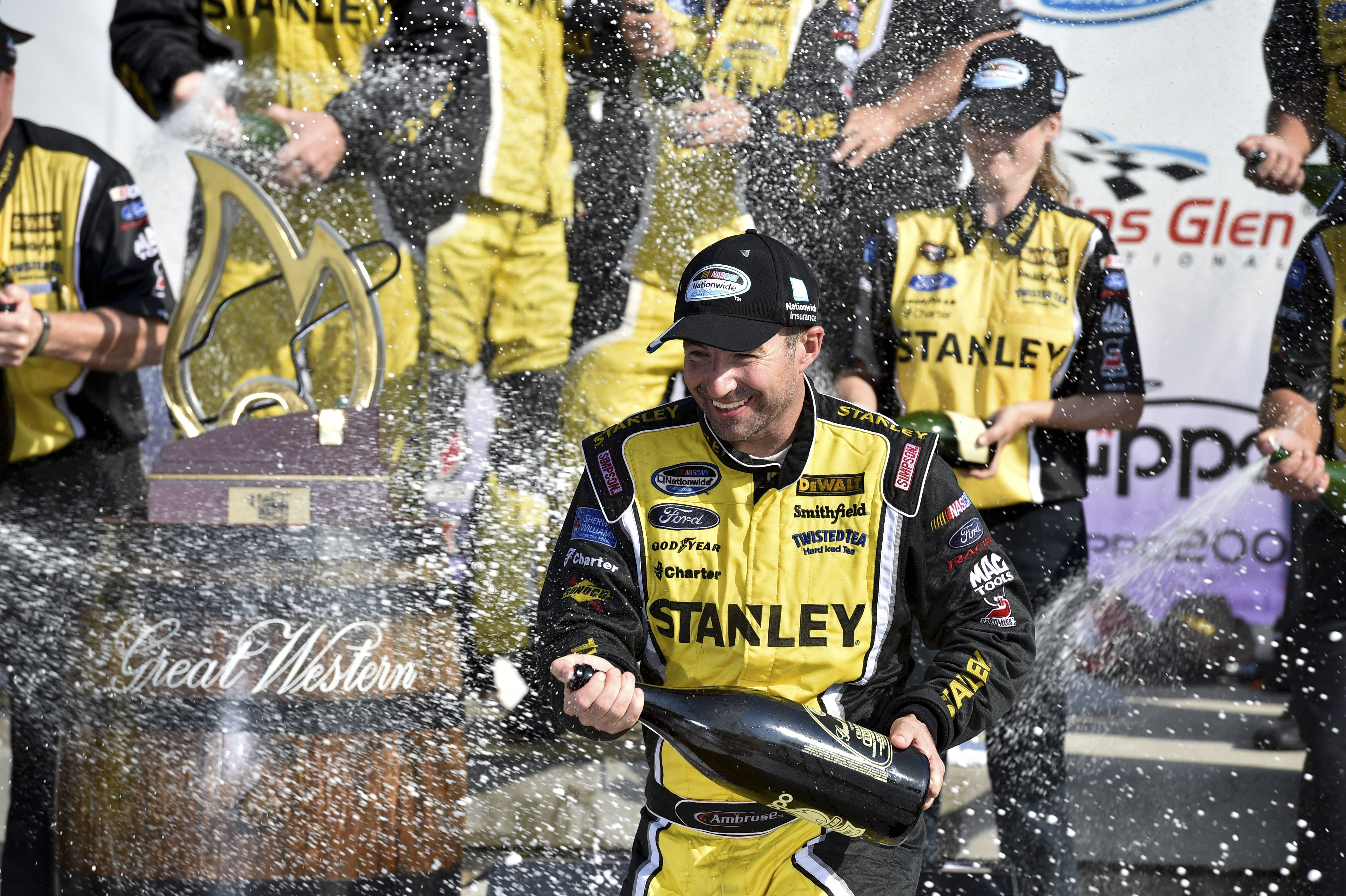 Marcos Ambrose celebrates in Victory Lane after winning a NASCAR Nationwide Series auto race at Watkins Glen International, Saturday, Aug. 9, 2014, in Watkins Glen N.Y.