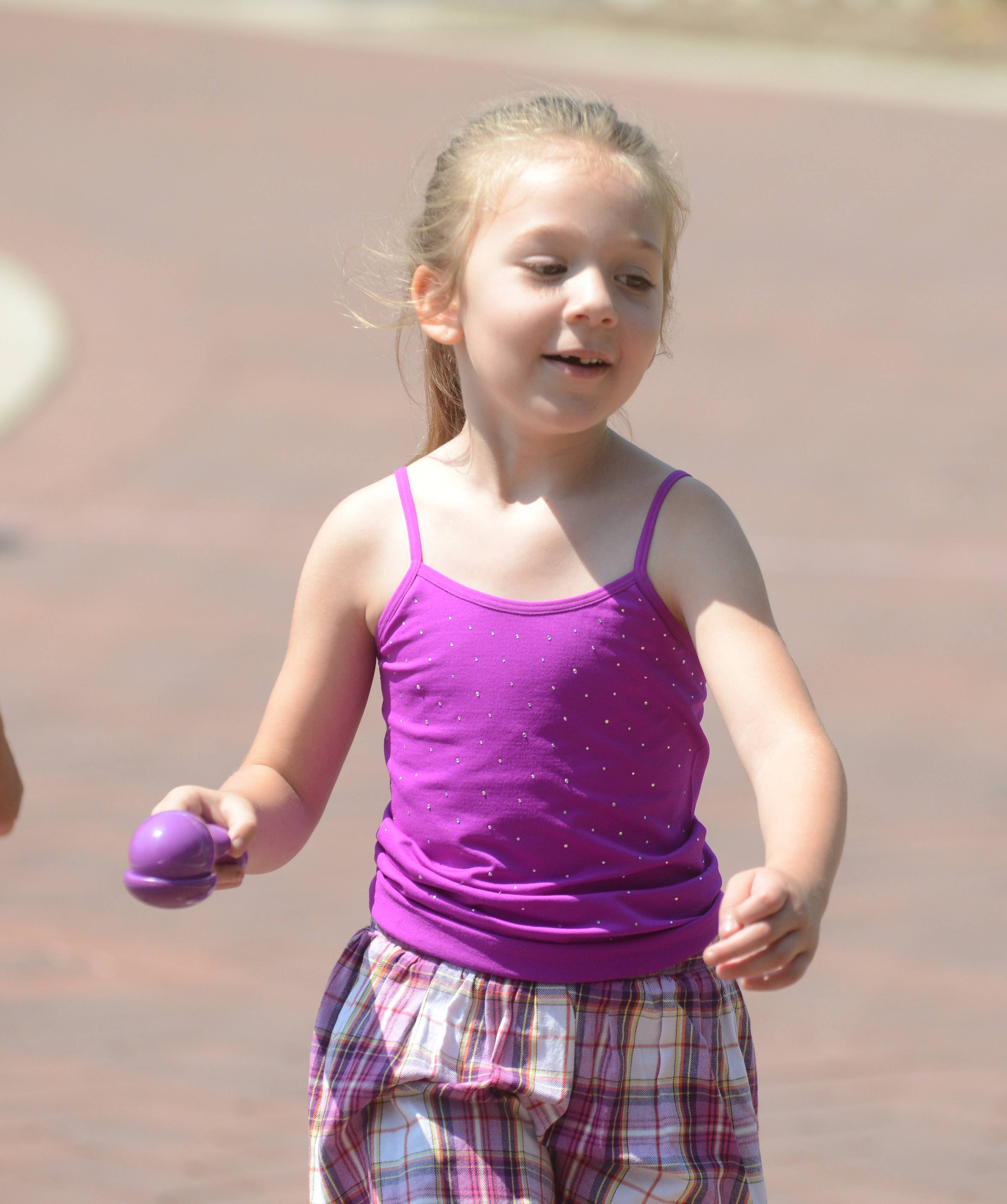 Amy Sclafani, 5, of Chicago plays the egg walk game at the Hometown Picnic at Naper Settlement in Naperville on Saturday.