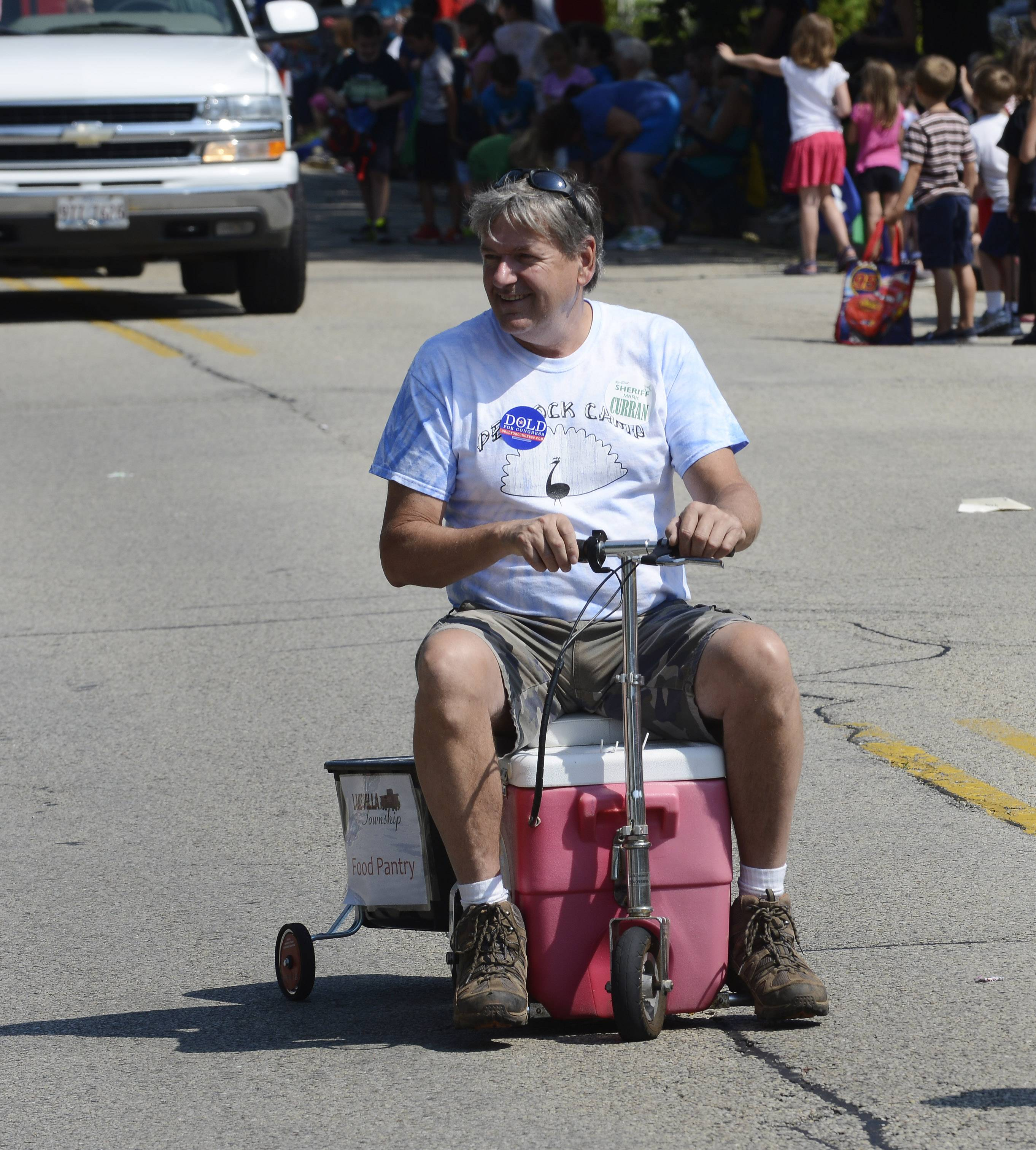 Lake Villa Township Supervisor Dan Venturi rides a self-propelled cooler while soliciting donations for the township food pantry Saturday during the Lindenfest Parade in Lindenhurst.