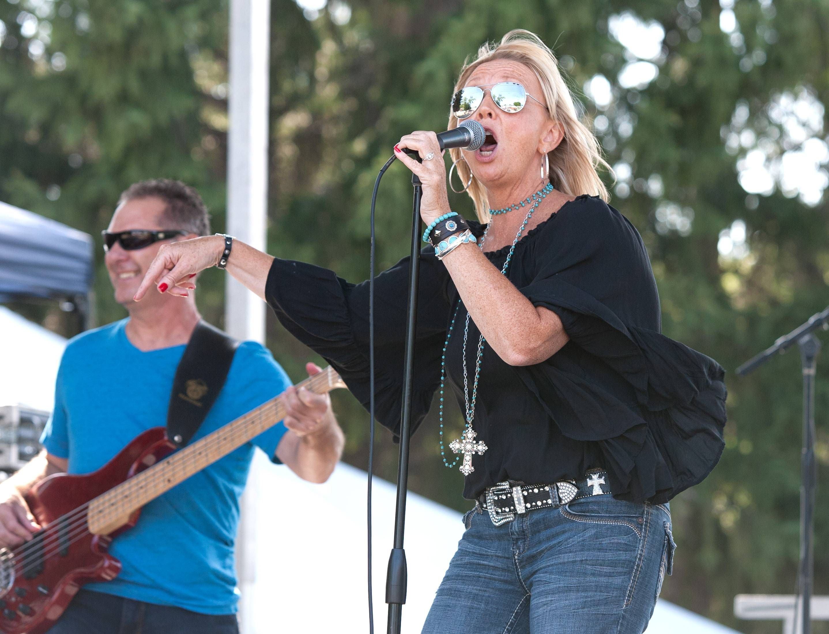 Kim Leffew of the Stilettos and Spurs Band entertains a Wood Dale Prairie Fest crowd with country-western music Saturday.