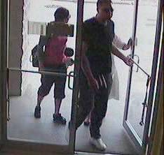 In this photo taken from a security camera at Petland, a man wearing a black shirt and sweatpants, a woman wearing black pants and a pink shirt and a second woman wearing a white sari are seen in the store. The store's owner says these are the three people last seen with the 3-month-old boxer from the store.