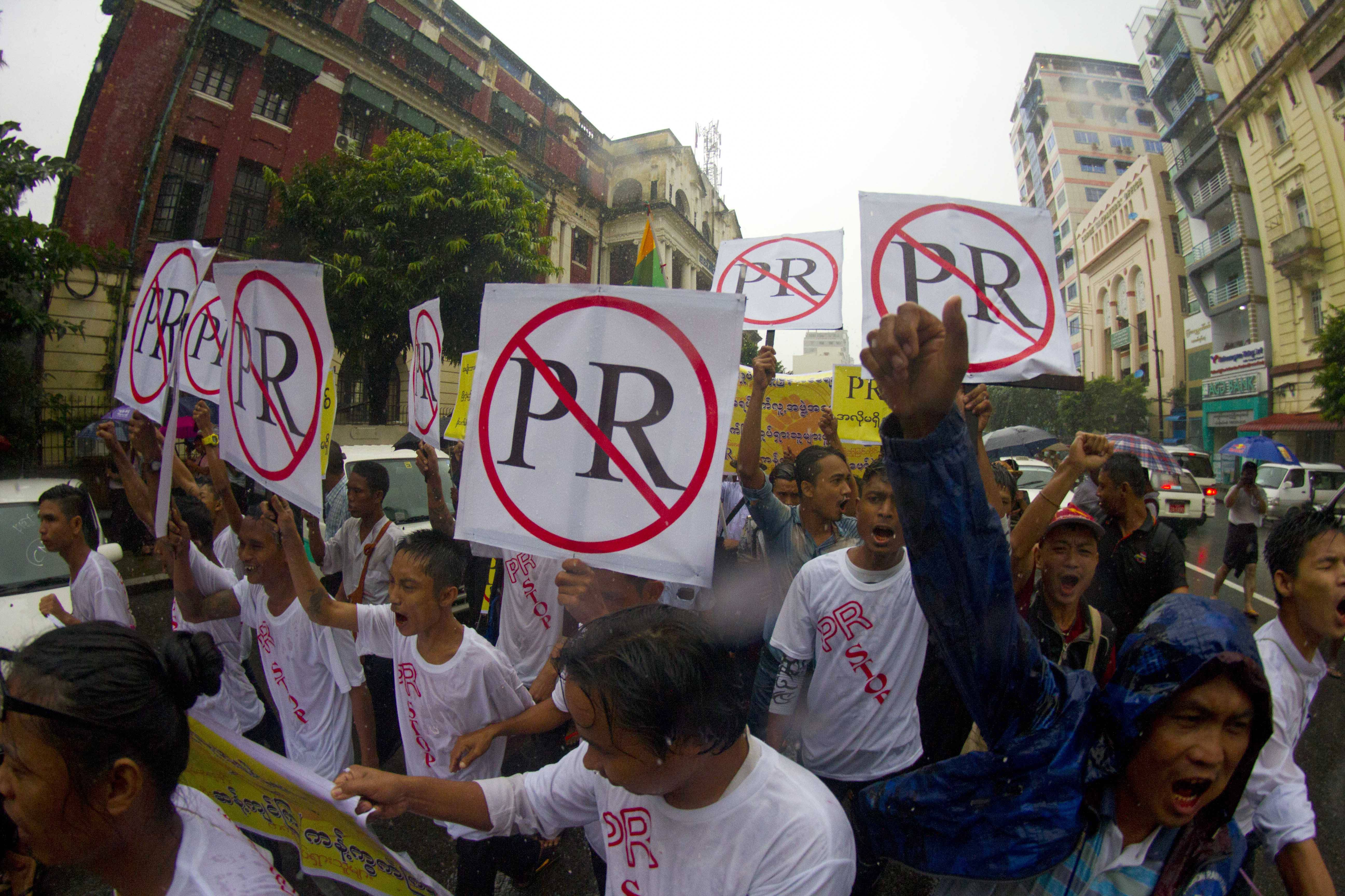 "Protesters hold placards and shout slogans  as they protest Tuesday against a ""proportional representation"" system in parliament, in Yangon, Myanmar. The country's main opposition party led by Aung San Suu Kyi and dozens of ethnic political parties strongly opposed to the PR system."