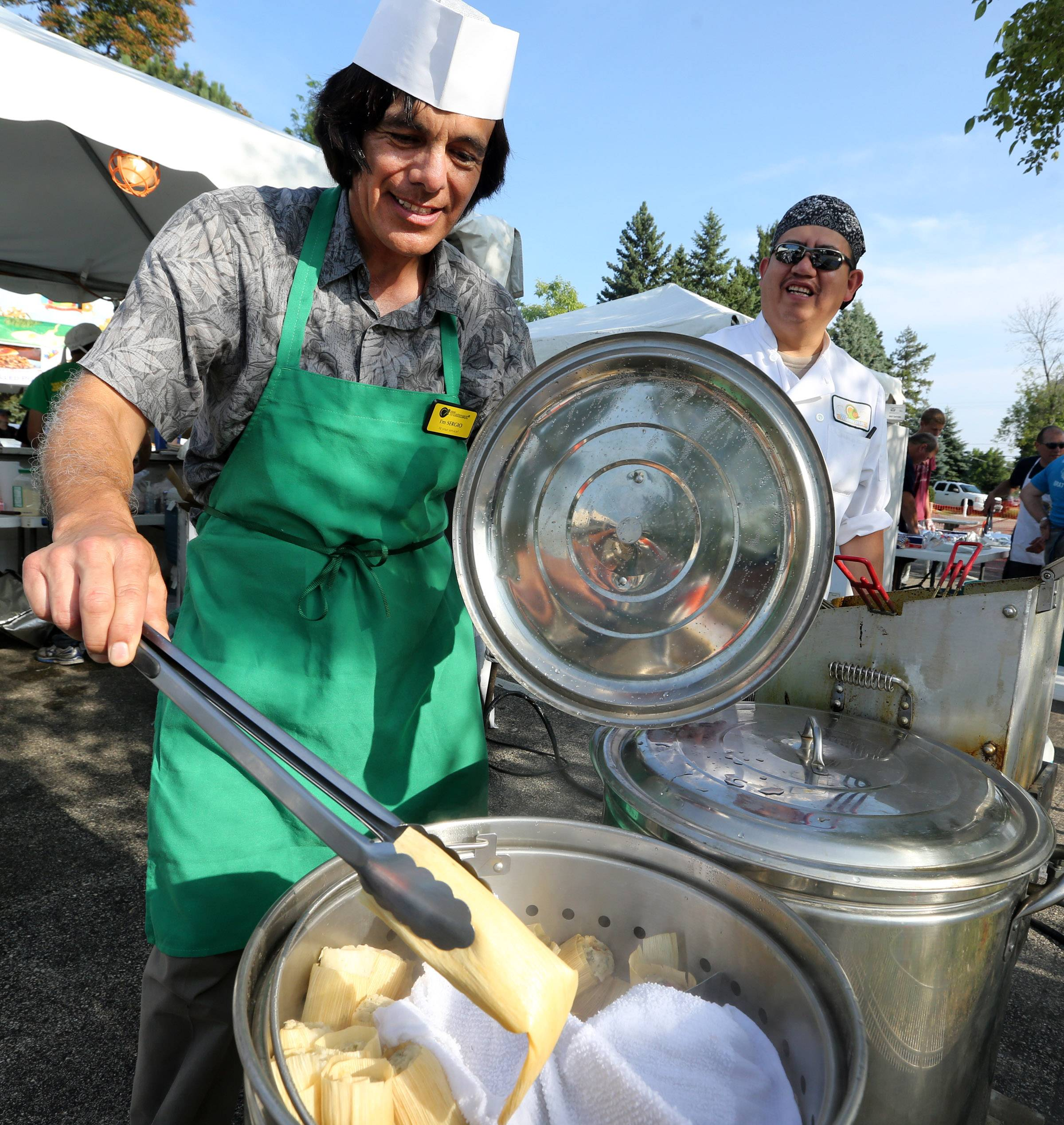 Sergio Rivera, owner of Momcorn in Gurnee, pulls a tamale out of a steamer at the second day of Gurnee Days on Friday.
