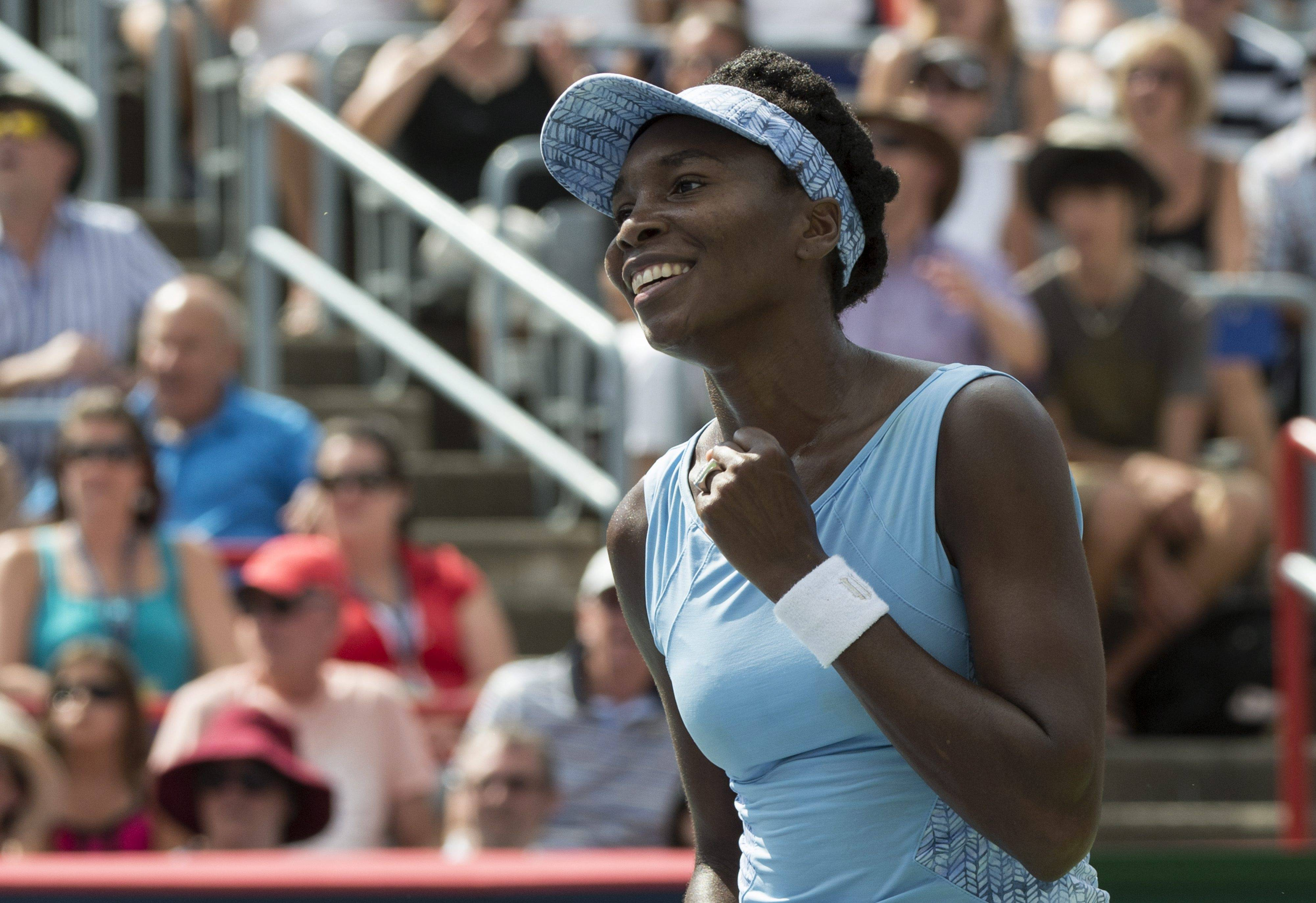 Venus Williams of the United States celebrates after beating her sister Serena 6-7, 6-2, 6-3 during semifinal play at the Rogers Cup tennis tournament Saturday, Aug. 9, 2014 in Montreal.