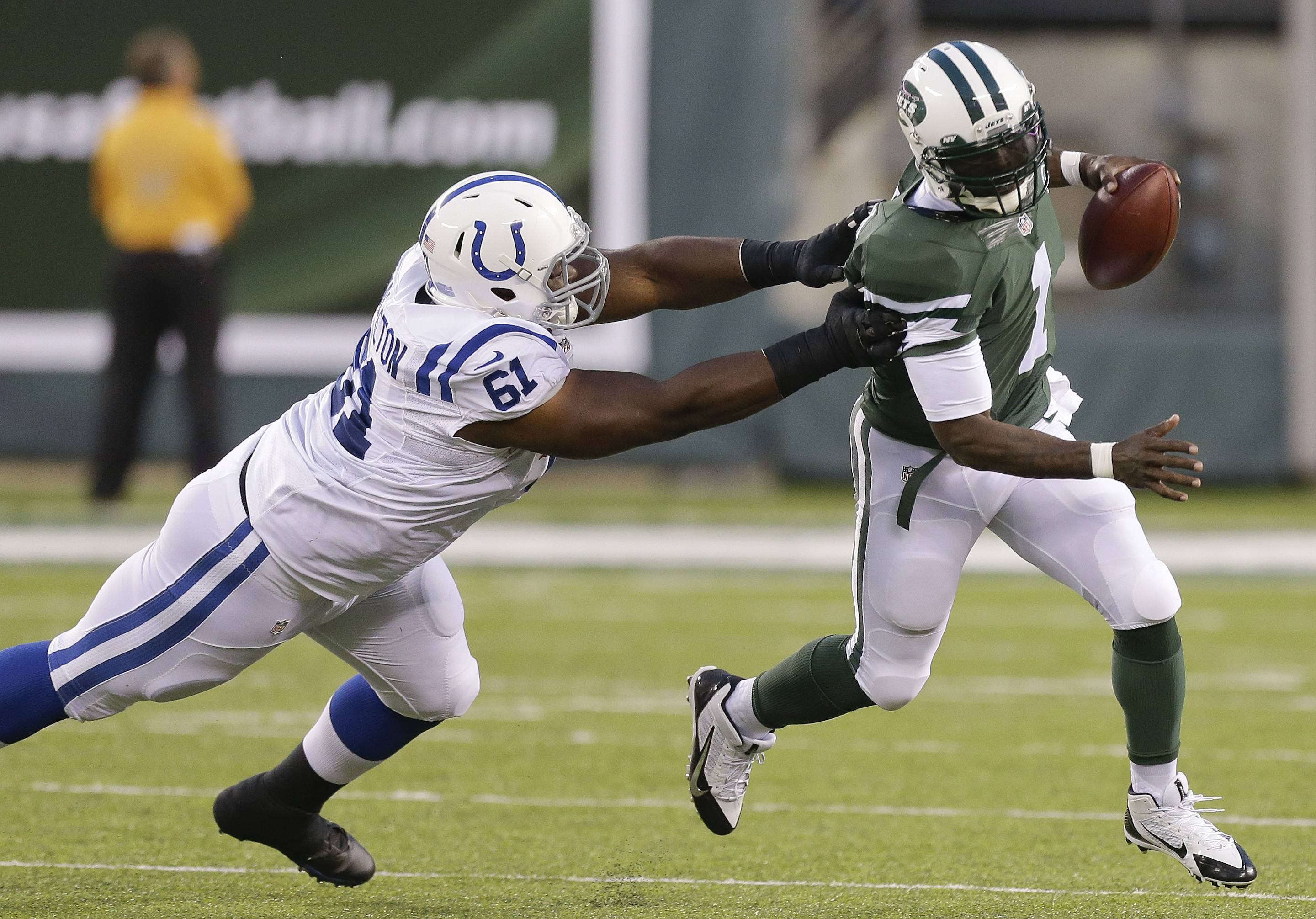 New York Jets quarterback Michael Vick (1) avoids Indianapolis Colts defensive tackle Jeris Pendleton (61) in the second quarter of a preseason NFL football game, Thursday, Aug. 7, 2014, in East Rutherford, N.J.