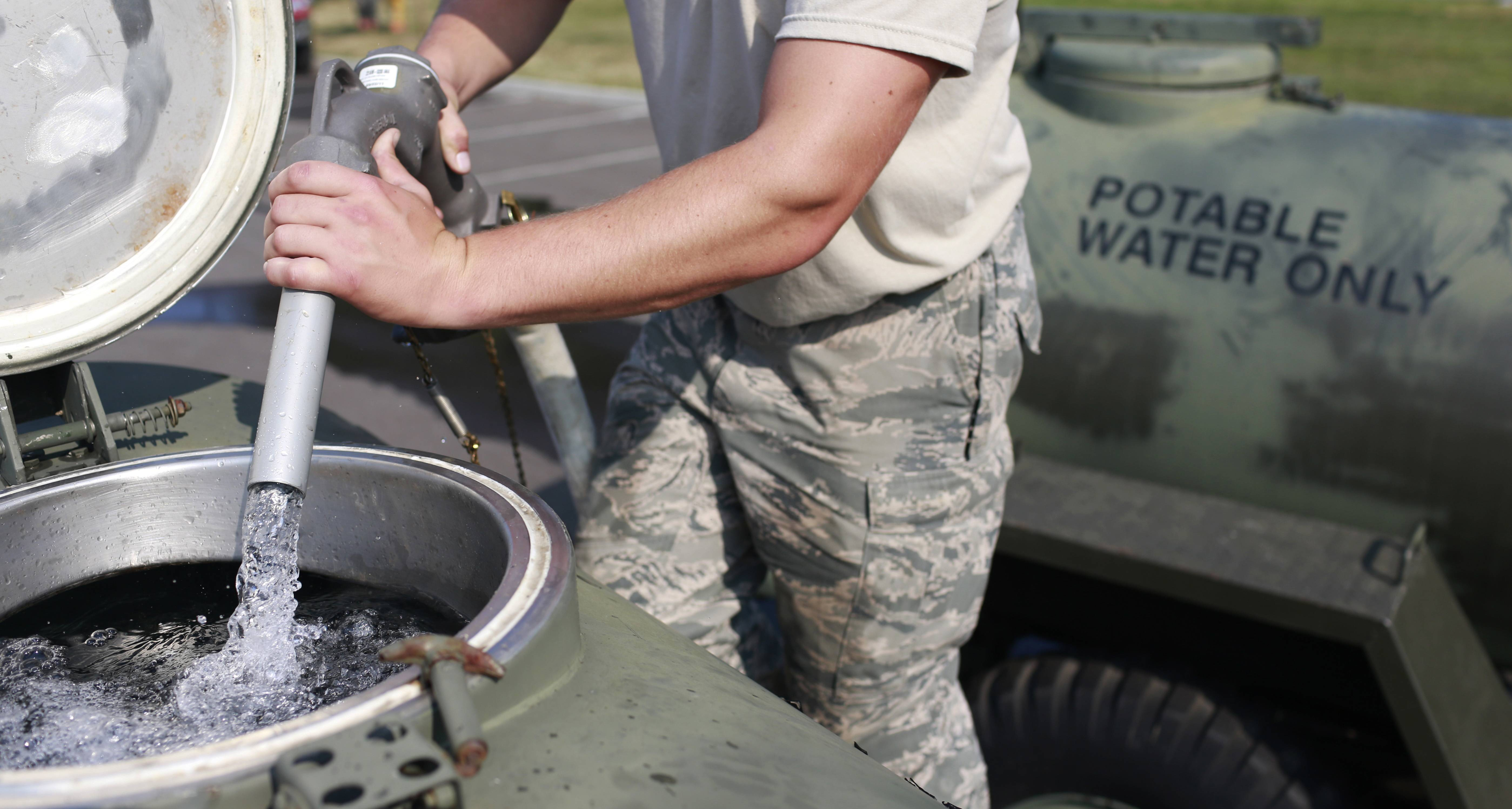 Ohio Air National Guard Senior Airman Nick Wander fills a 400 gallon military water buffalo with fresh drinking water at Woodward High School in Toledo, Ohio., Aug. 3. Environmentalists, scientists and farmers agree that agriculture runoff is feeding the blue-green algae blooms on Lake Erie that are linked to the toxins found in the drinking water of 400,000 people last weekend.