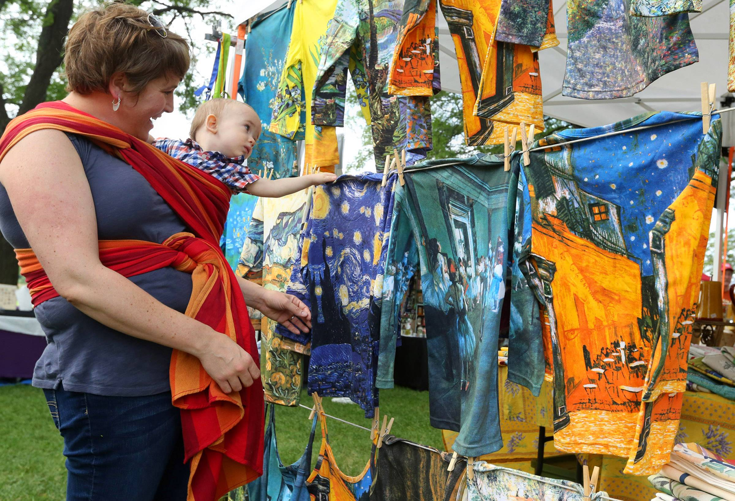 Meredith Entler's 1-year-old son, Duncan, is mesmerized Sunday by colorful famous painting printed on shirts at Elizabeth Eischeid's Cadeaux de Madeleine booth at the annual French Connection Day celebration at Cantigny Park in Wheaton.