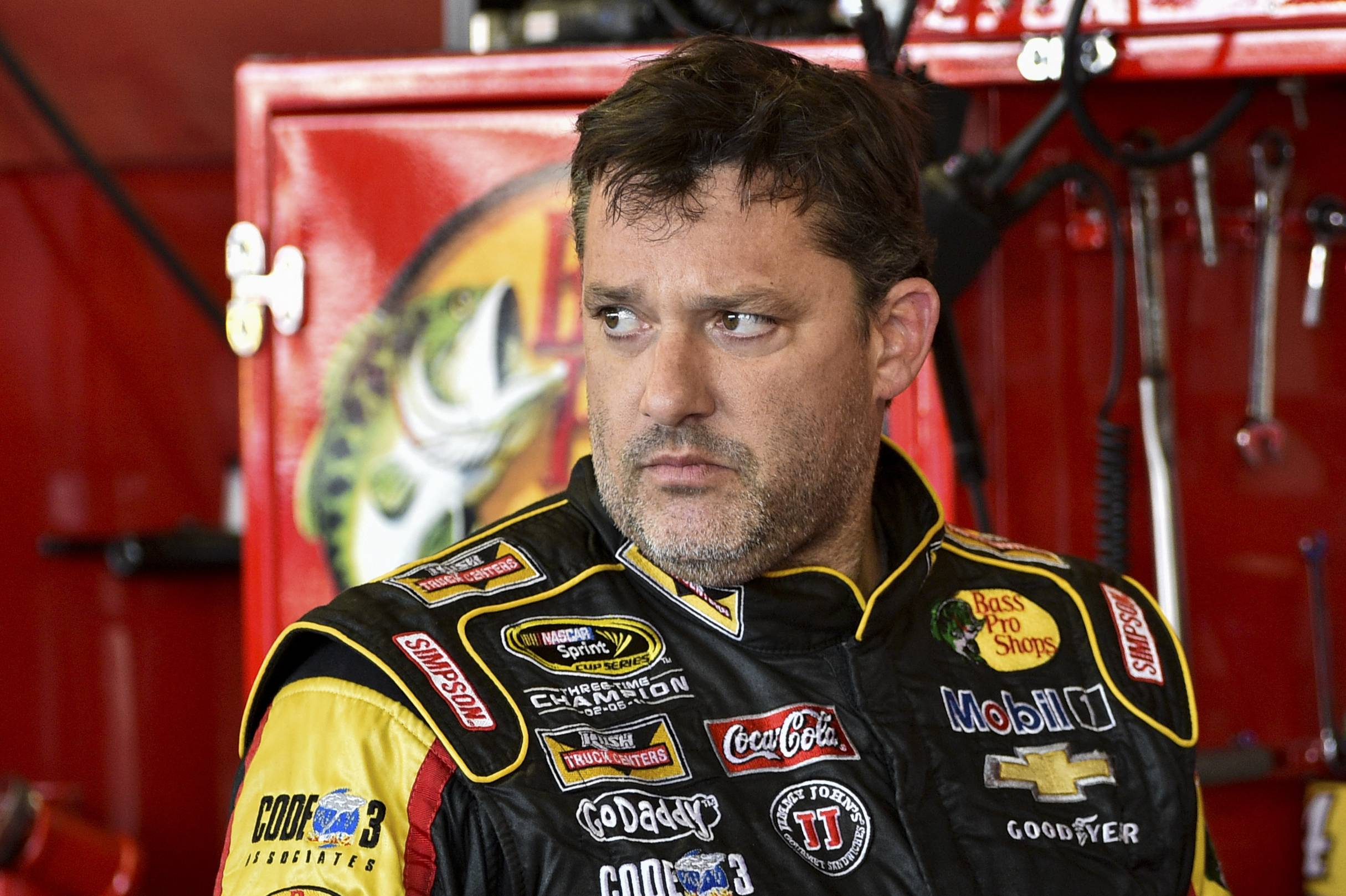 "In this Friday, Aug. 8, 2014, photograph, Tony Stewart stands in the garage area after a practice session for Sunday's NASCAR Sprint Cup Series auto race at Watkins Glen International, in Watkins Glen N.Y. Stewart struck and killed Kevin Ward Jr., 20, a sprint car driver who had climbed from his car and was on the track trying to confront Stewart during a race at Canandaigua Motorsports Park in upstate New York on Saturday night. Ontario County Sheriff Philip Povero said his department's investigation is not criminal and that Stewart was ""fully cooperative"" and appeared ""very upset"" over what had happened."