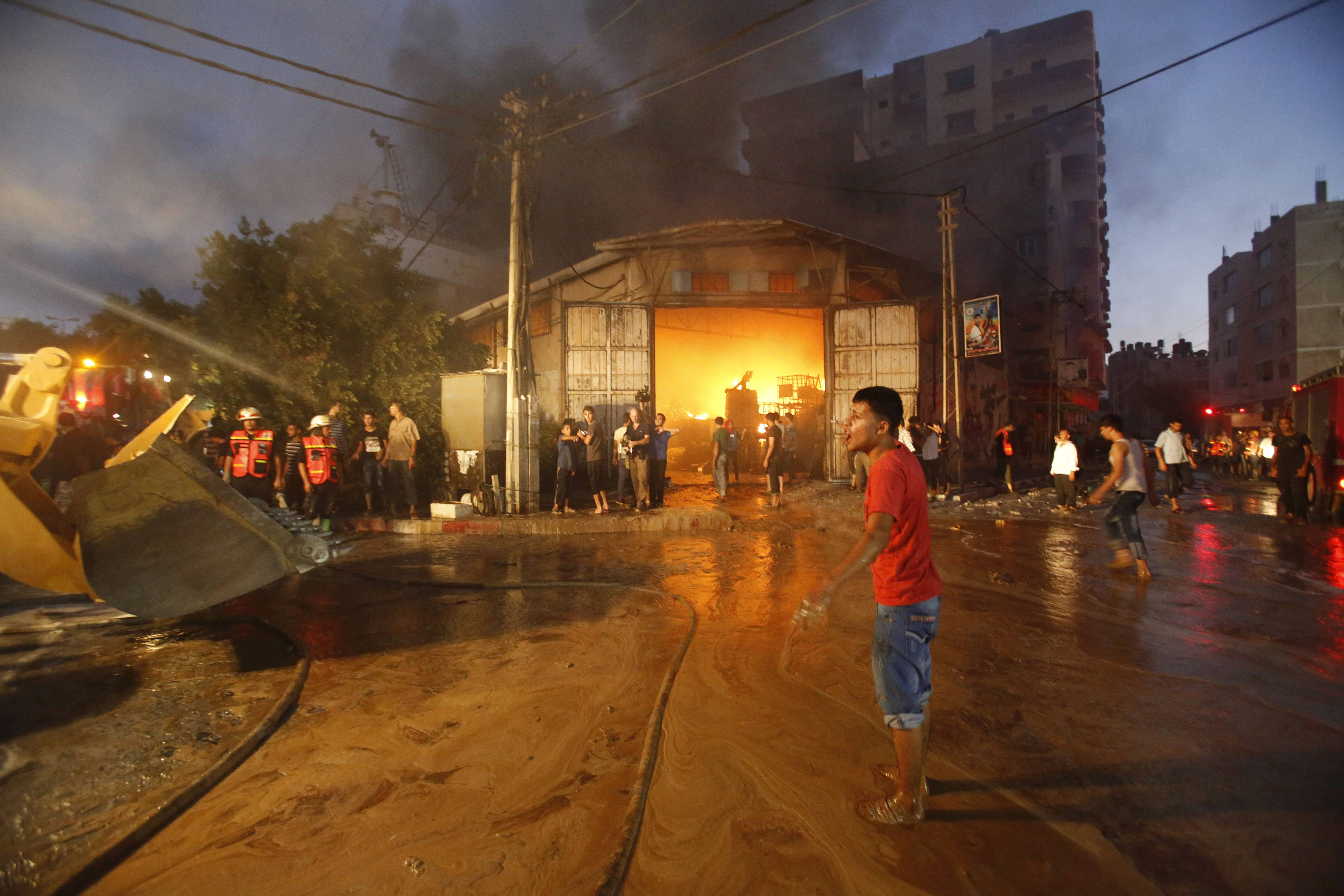 Firefighters try to extinguish fire after a cleaning materials factory was hit by an Israeli airstrike in Gaza City on Sunday.