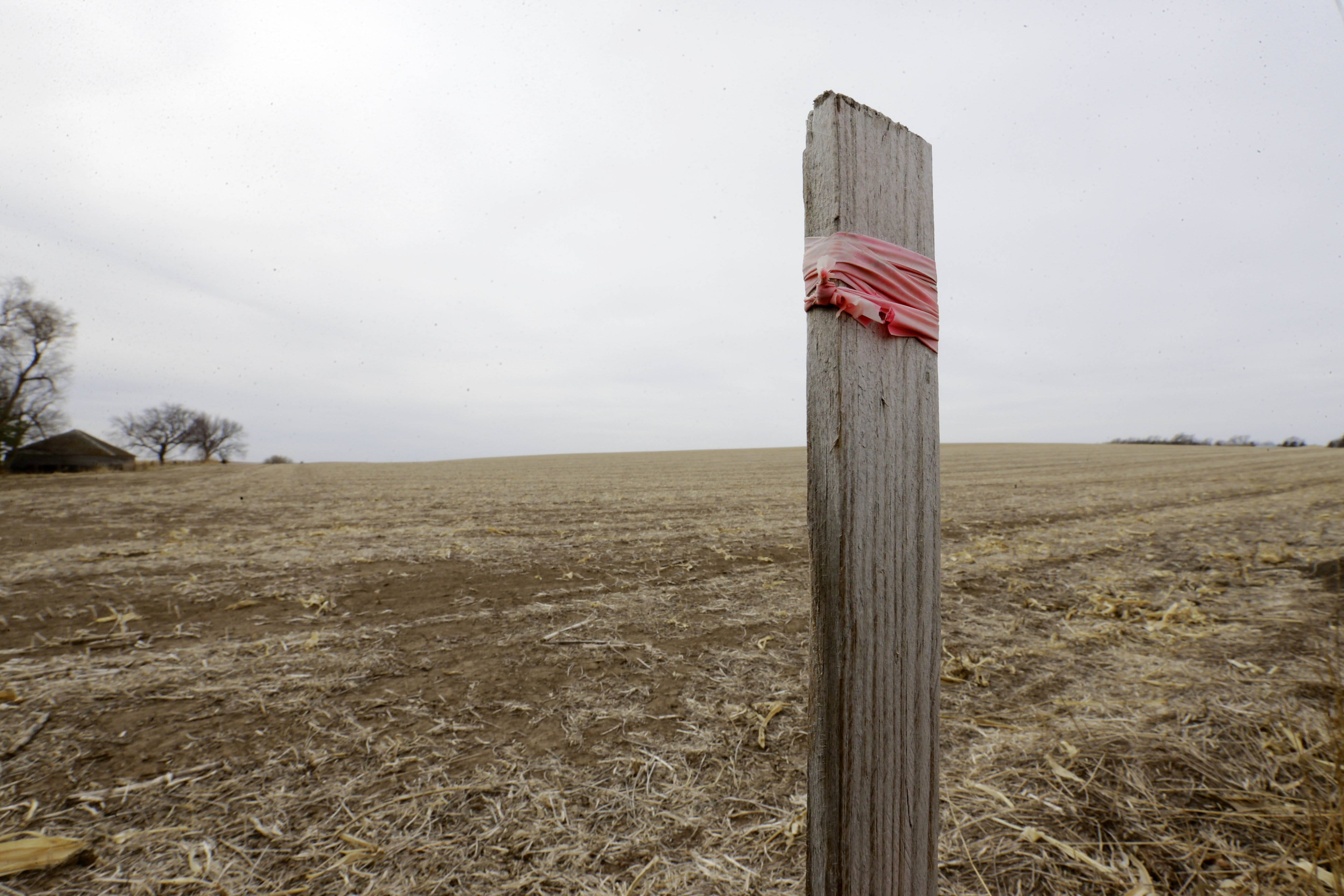 This March 17, 2014, photo shows a stake in the ground that marks the route of the Keystone XL pipeline in Tilden, Neb. The much-debated Keystone XL pipeline could produce four times more global warming pollution than the State Department has calculated, according to scientists at a Swedish research facility.