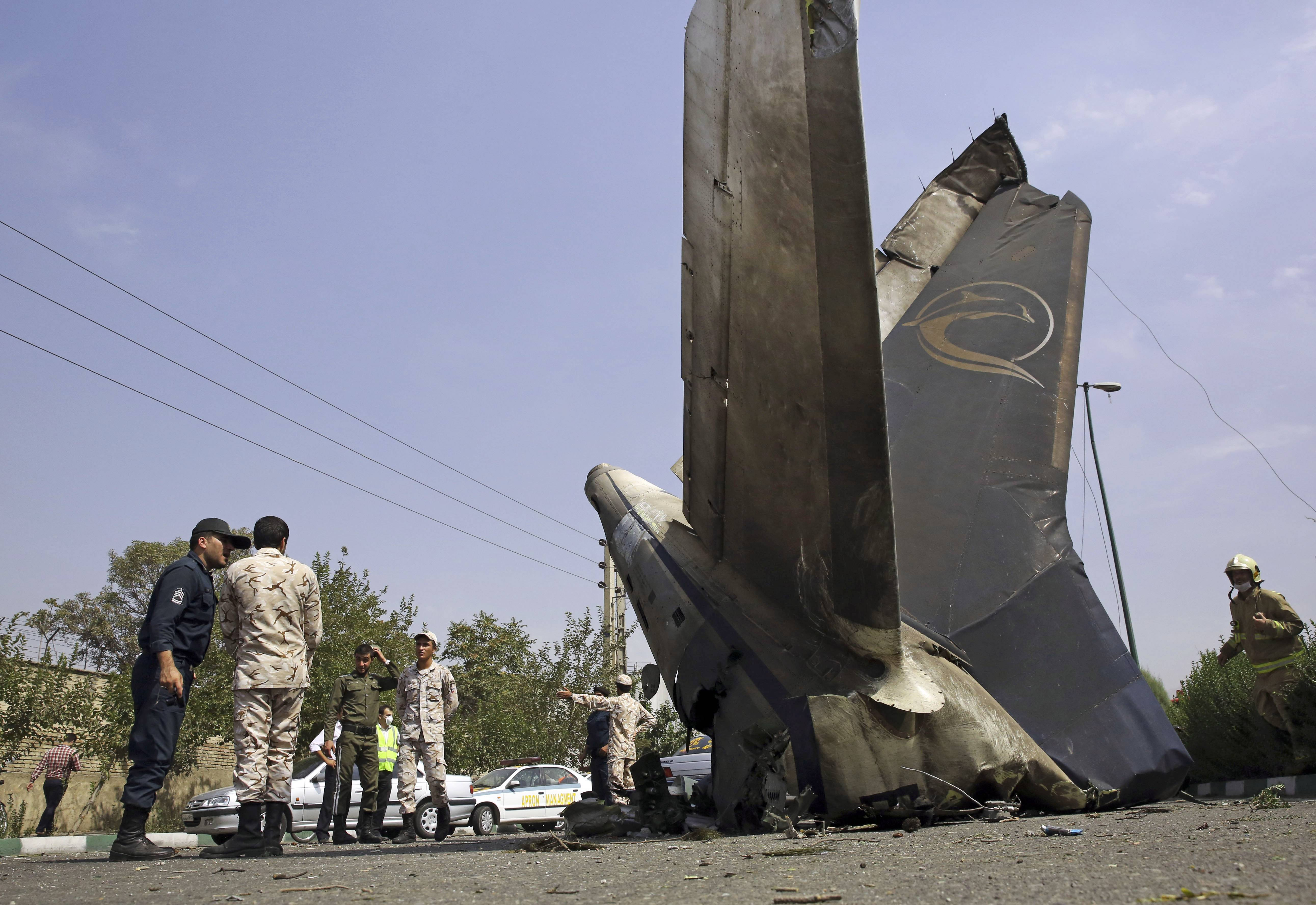 Iranian Revolutionary Guards inspect the site of a passenger plane crash near the capital Tehran, Iran, Sunday.