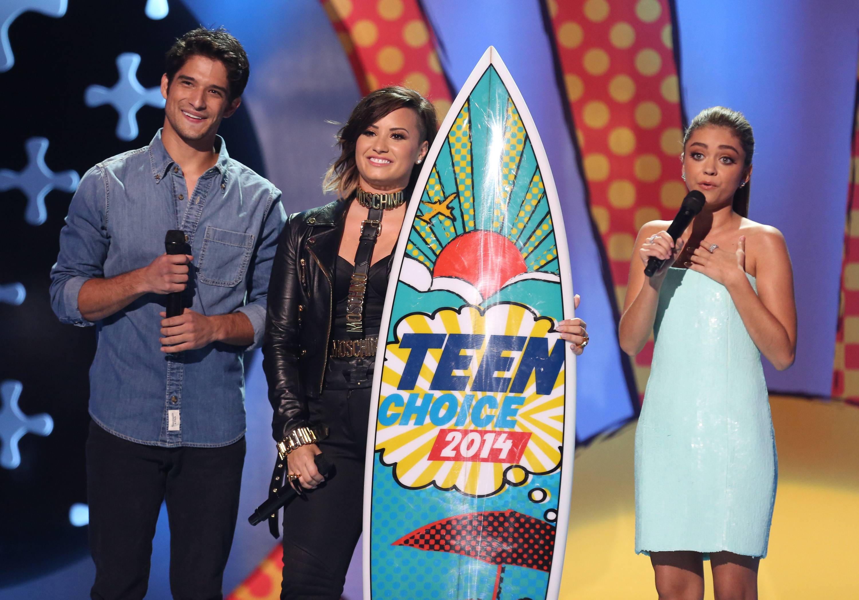 "Tyler Posey, left, and Sarah Hyland, right, present the award to Demi Lovato for choice summer song for ""Really Don't Care"" and choice summer music star: female at the Teen Choice Awards at the Shrine Auditorium on Sunday in Los Angeles."
