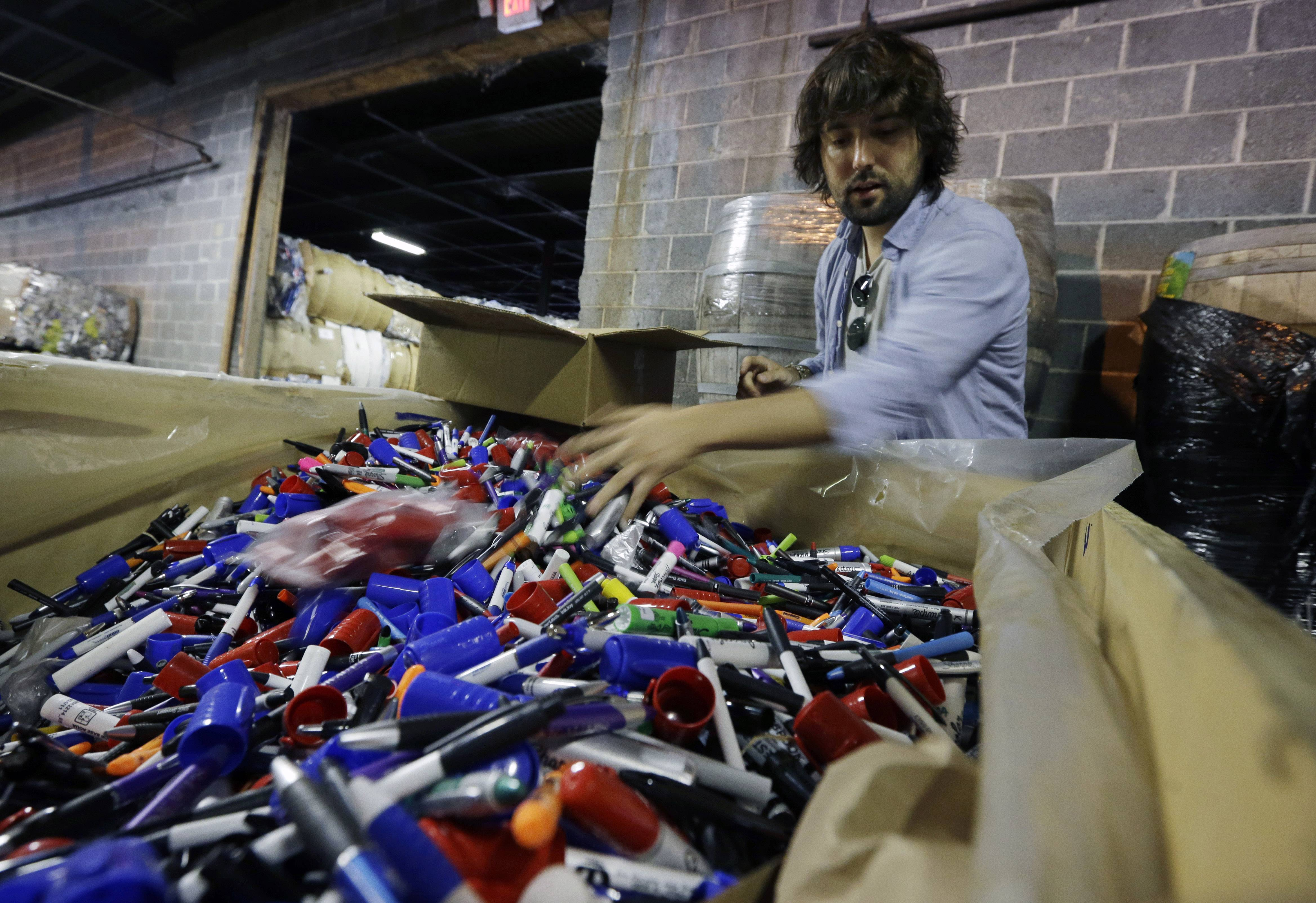 TerraCycle Inc. founder Tom Szaky stands in a warehouse, as he looks through a large box of marker pens Tuesday, Aug. 5, 2014, in Trenton, N.J. Founded in 2001 by then-20-year-old Princeton student Szaky, TerraCycle works to collect and transform a range of hard-to-recyle items, from potato chip bags to cigarette butts, into colorful consumer products. A new reality show launching Aug. 8 will focus on the New Jersey-based recycling company.