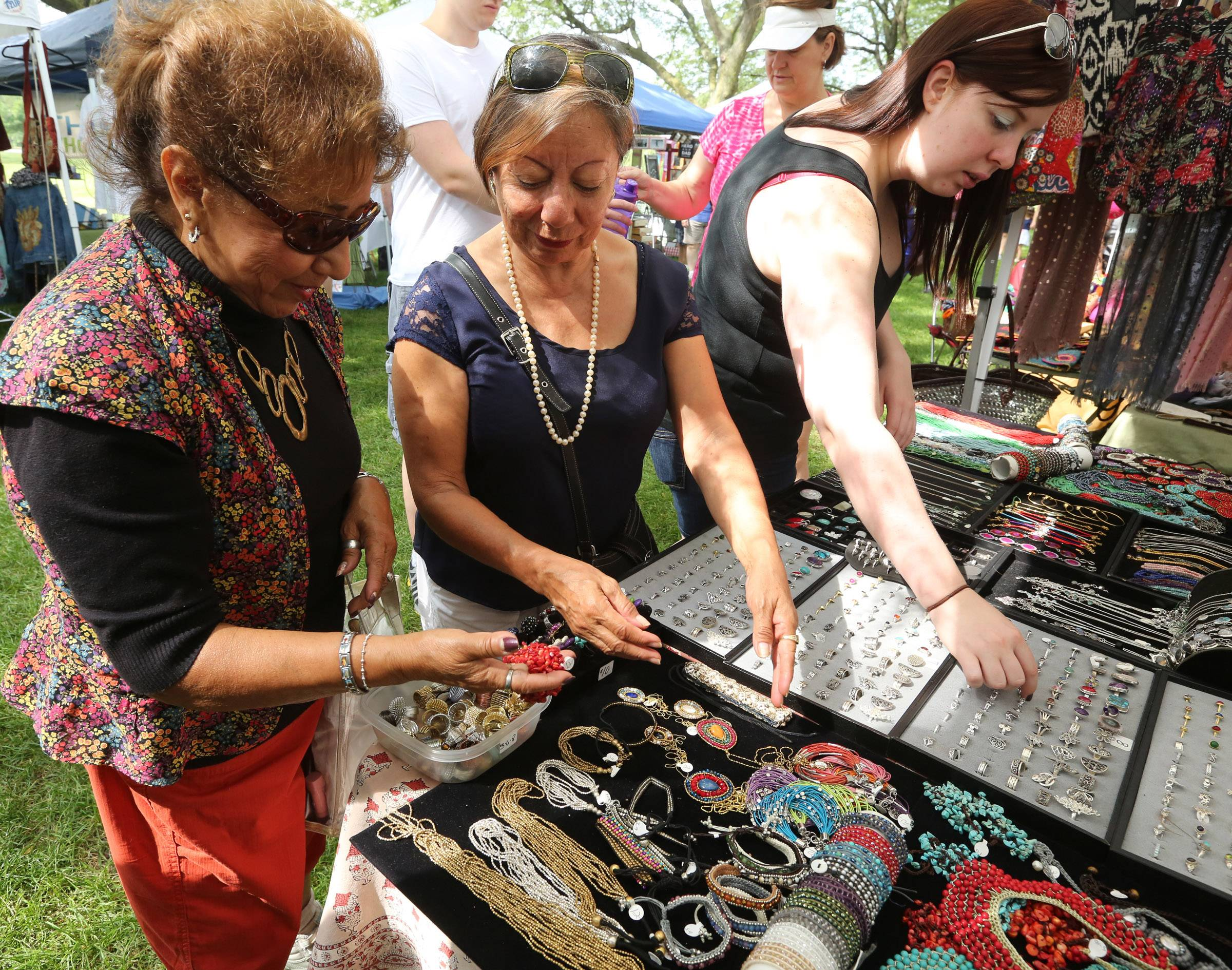 Rosa Castro, left, and Margarita Guerrero, both of Chicago, look at jewelry by Christine Mitchell during Sunday's French Connection Day celebration at Cantigny Park in Wheaton.