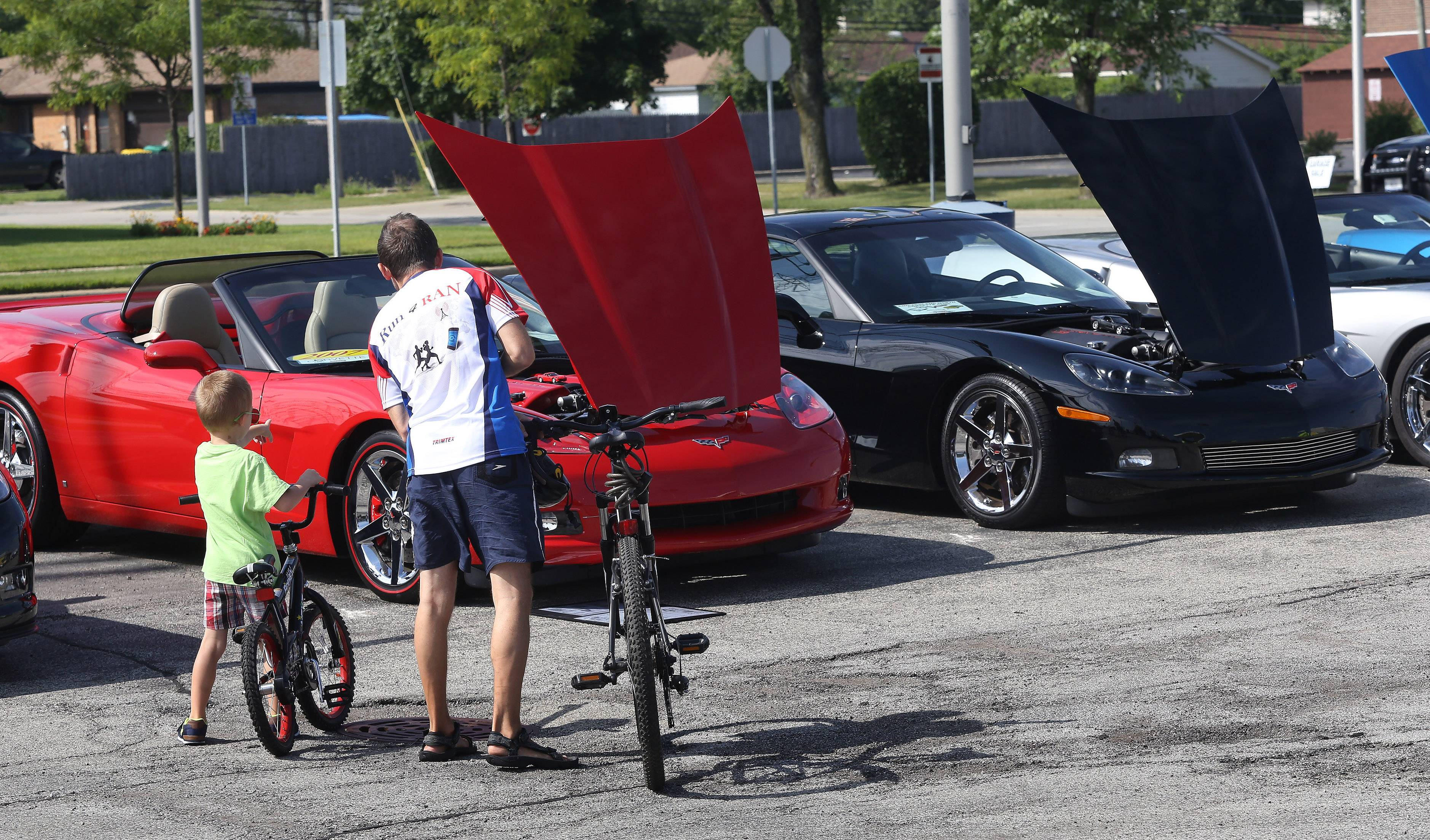 Wheeling residents Iwo Angelow and his son, Jakub, 5, look at several Corvettes during the 9th Annual All-Corvette Show Sunday at Bill Stasek Chevrolet in Wheeling. The show was sponsored by the Chicagoland North Corvette Club and featured over 100 Corvettes from as early as 1960.
