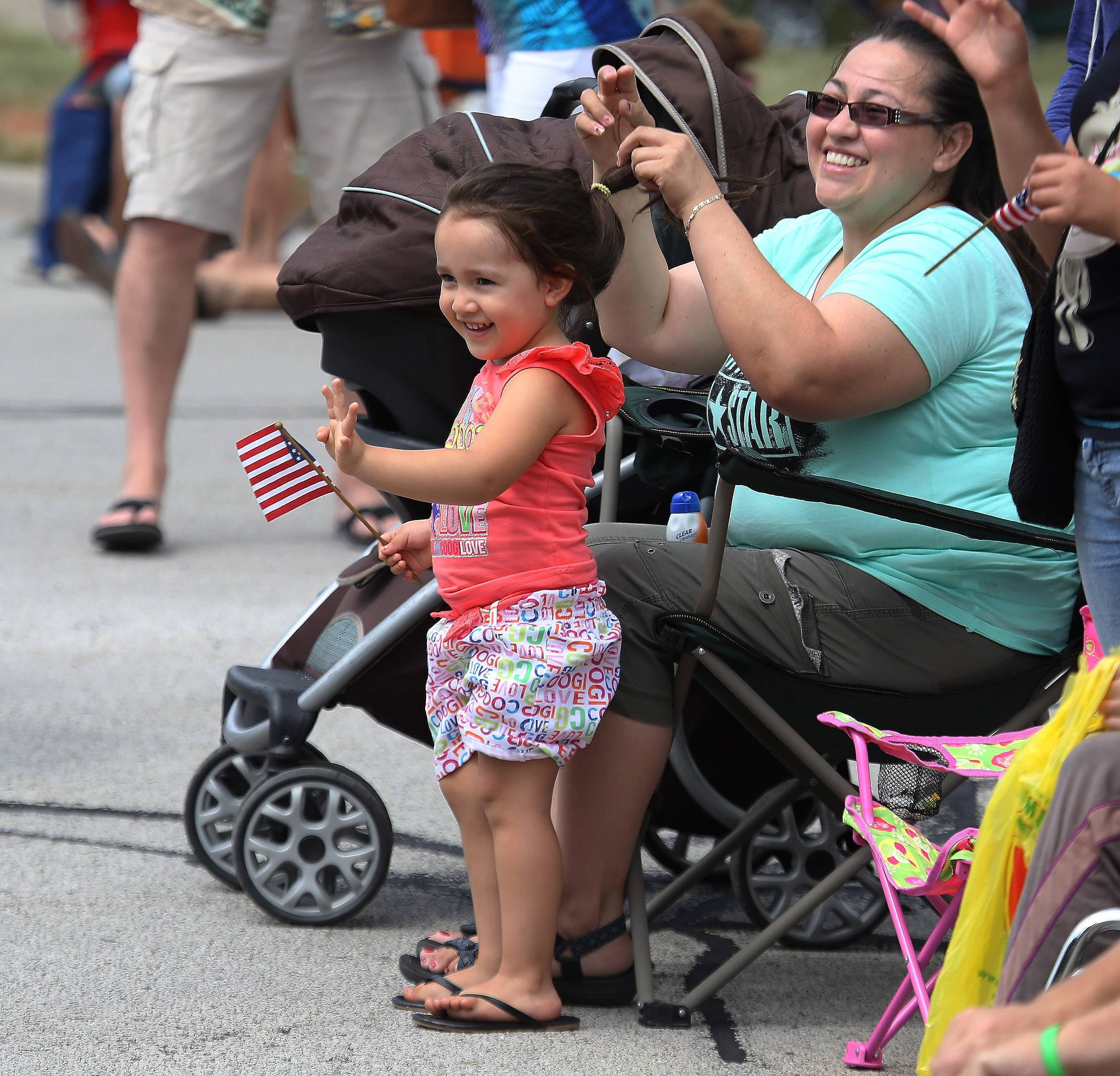 "Three-year-old Isabella Ortiz and her mother, Emma, of Waukegan wave at firefighters riding in the parade during the Gurnee Days parade Sunday along Old Grand Ave. This year's theme was ""A Lil' Bit of Country, A Lil' Bit of Rock and Roll."""