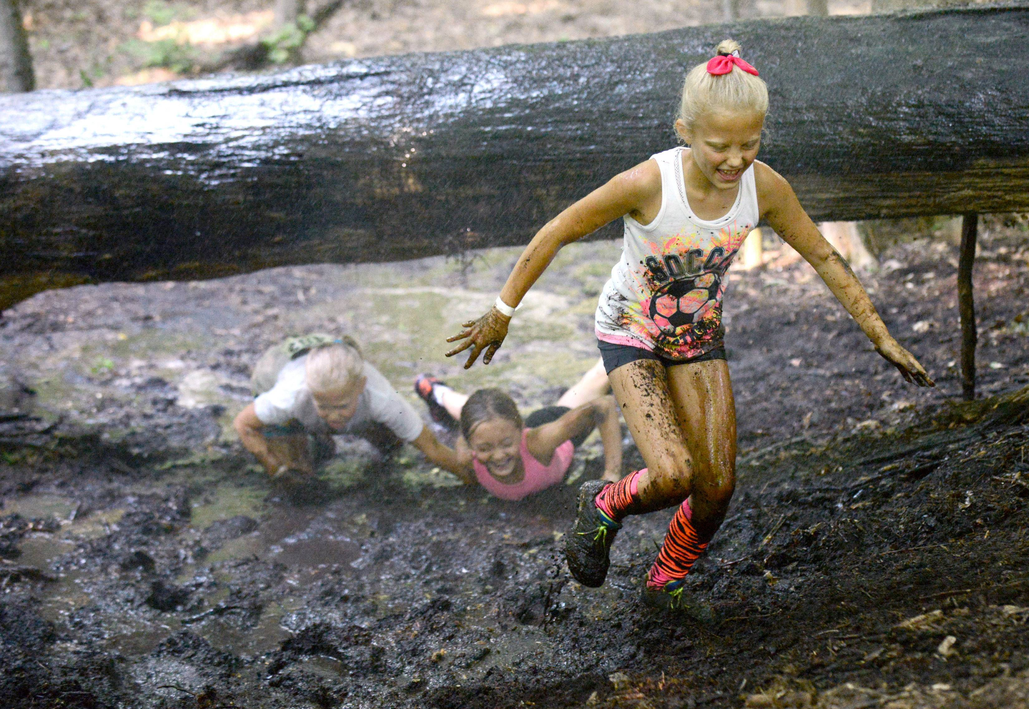 Elizabeth Johnson, 8, of Huntley, rises from the mud as her sister Annabel, 11, left, and friend Ava Ullrich, 9, also of Huntley, crawl under a tree limb in the Mud 'N Fun Viking Run at Good Templar Park in Geneva on Saturday. The trio had so much fun, they went through the mud a second time.