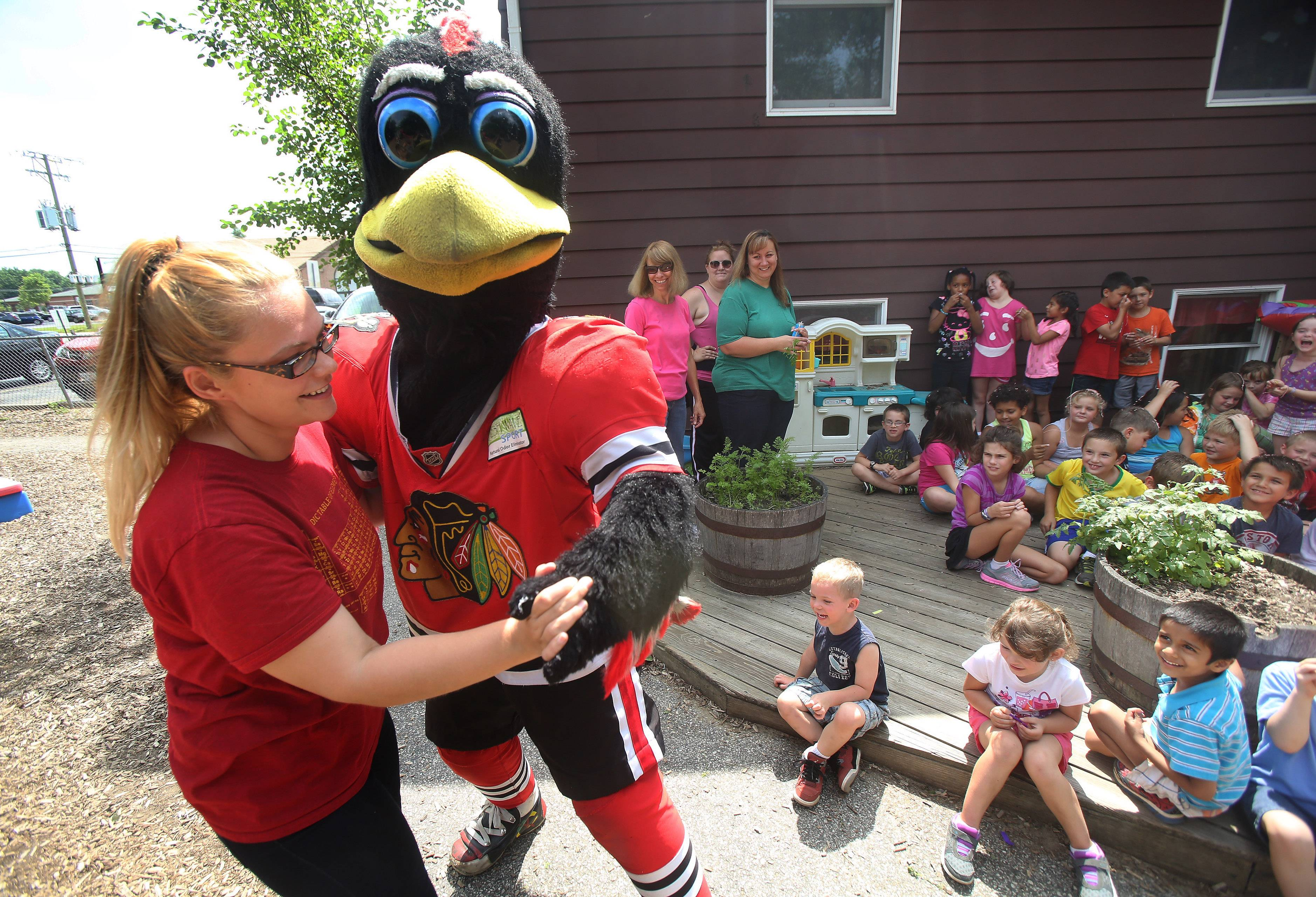 "The Chicago Blackhawks mascot Tommy Hawk dances with prekindergarten teacher Brittany Ankney as he entertained children at the Lindenhurst Early Childhood Learning Center on Monday. The center was celebrating ""Chicago Week"" with plans to eat deep dish pizza and go downtown to tour Chicago later this week."
