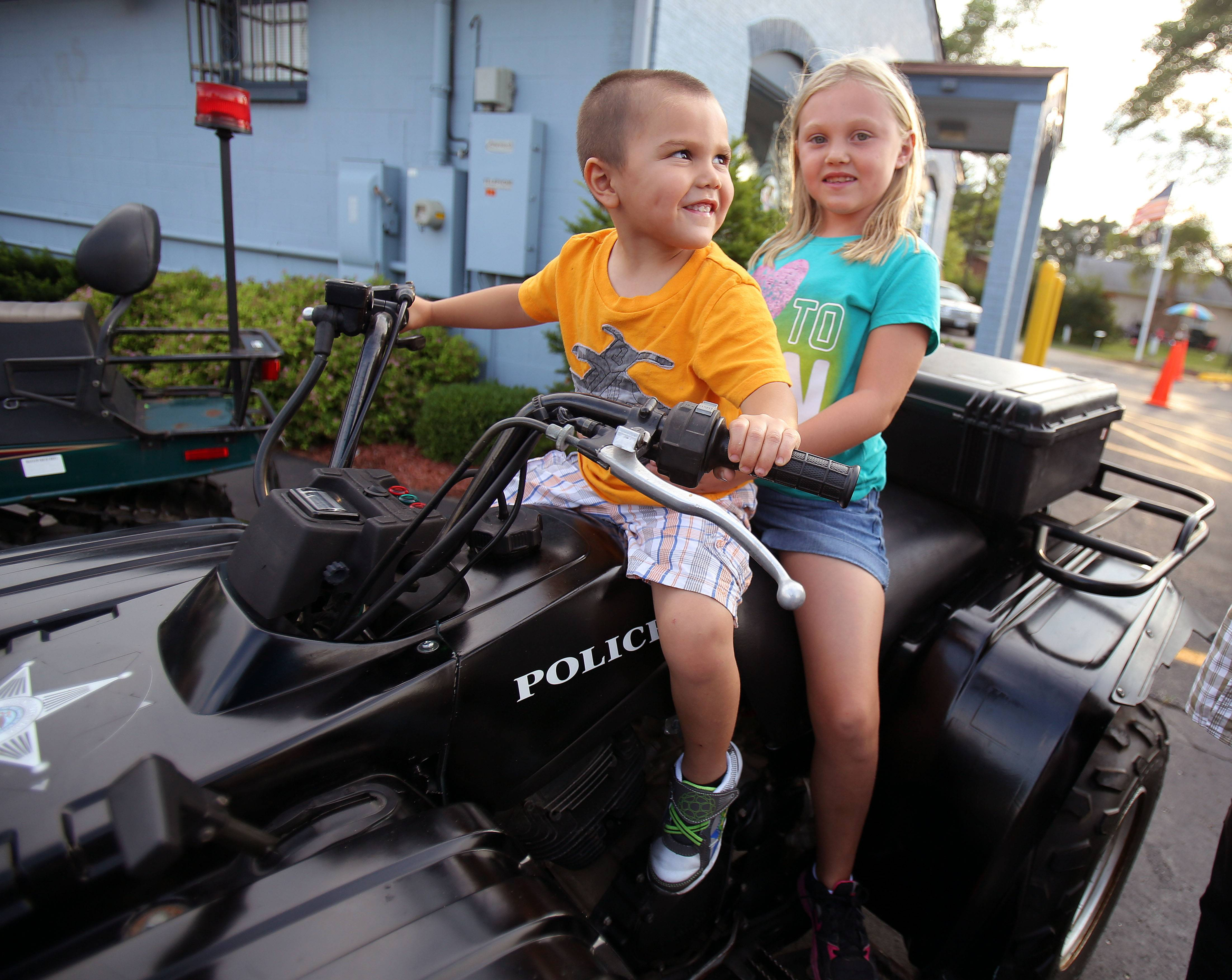 Bradley Sobecki, 3 and his sister Grace, 8, both of Fox Lake, sit on a police 4-wheeler during National Night Out at the Round Lake Park Police Department Tuesday night.