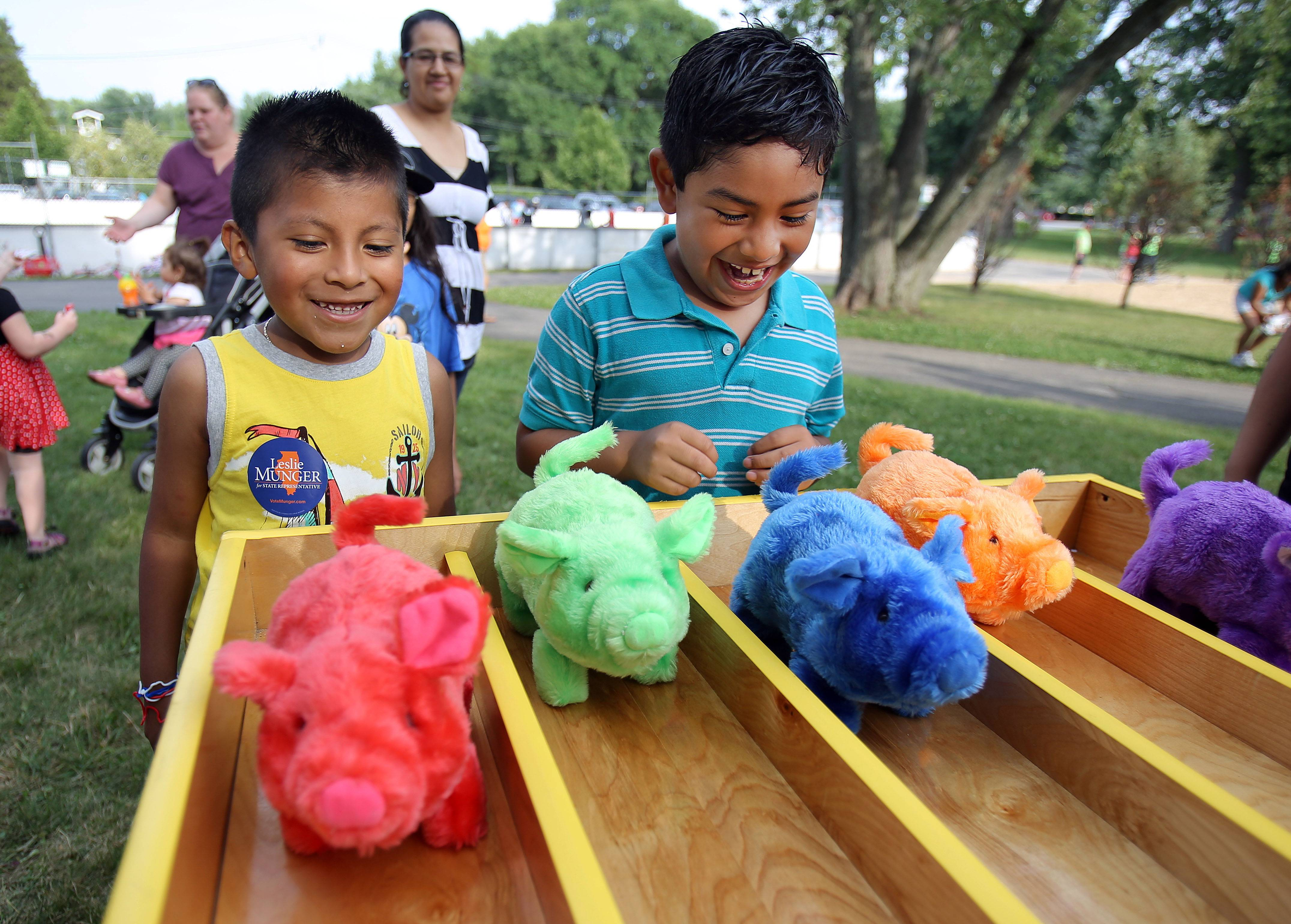 5-year-old Jesus Beronca, left, and 6-year-old Alonso Roman, both of Vernon Hills play a game called Pork Chop Speedway during National Night Out at Hartmann Park in Vernon Hills Tuesday night.