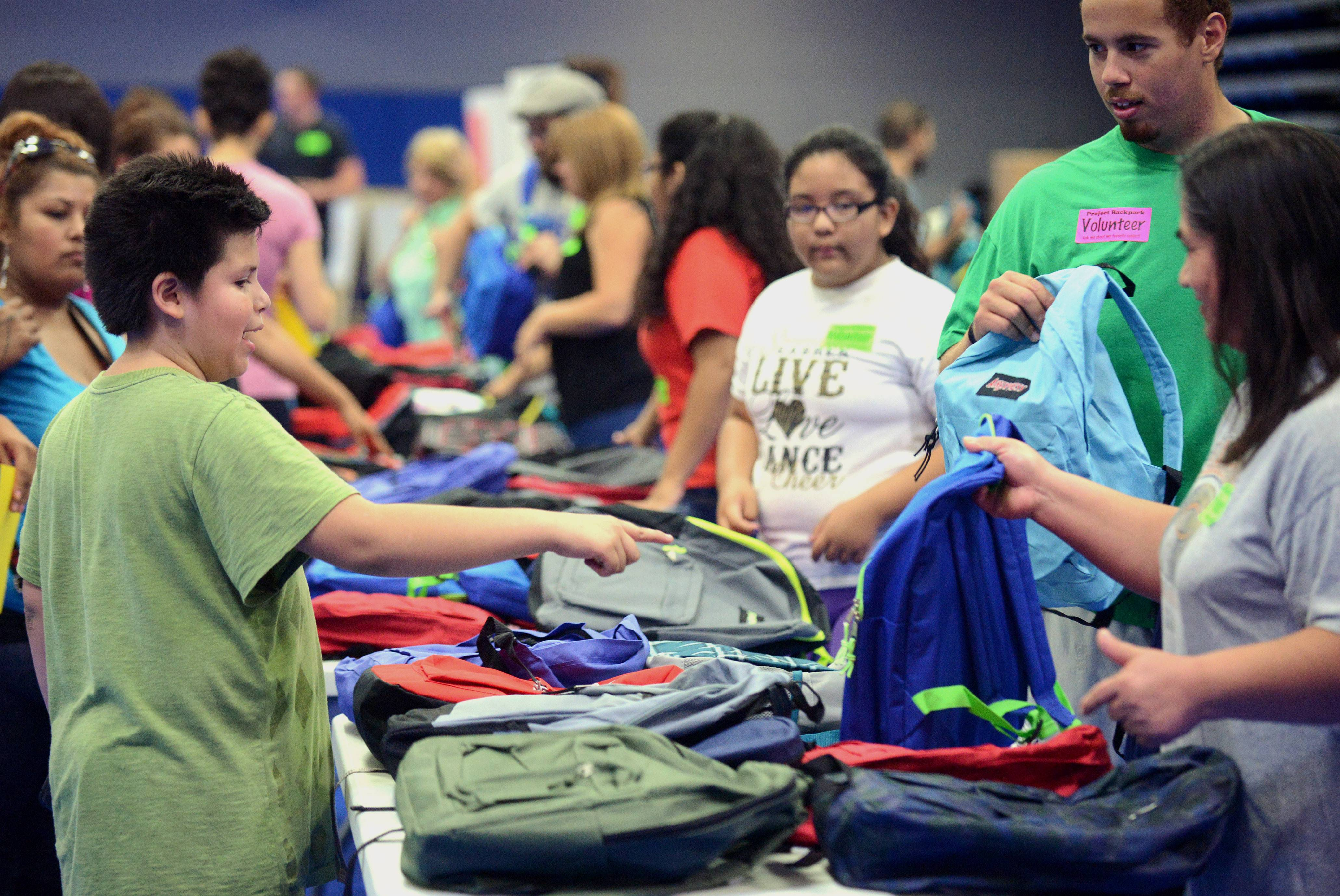 Moises Villa, 11, of Elgin picks the bag he wants at the Project Backpack giveaway event at Elgin Community College on Saturday. The free school supplies and backpacks were on a first-come, first-served basis to local students. Moises is going into sixth grade this fall.