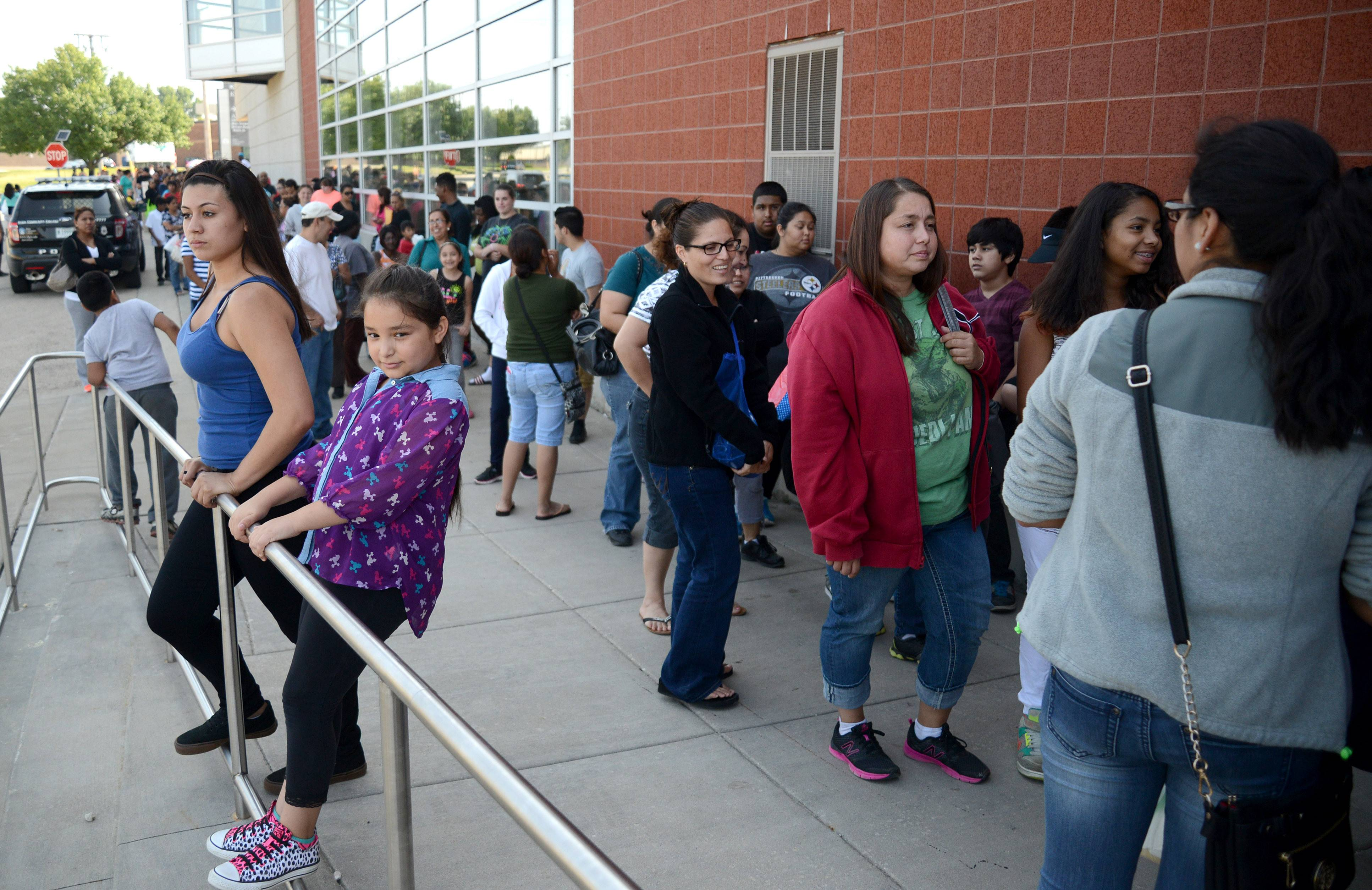 Beatriz Farias, 13, left, and Guadalupe Navarette, 9, both of Carpentersville, wait in the long line for the Project Backpack event at Elgin Community College on Saturday. The free school supplies and backpacks were distributes on a first-come, first-served basis to students enrolled in local schools.
