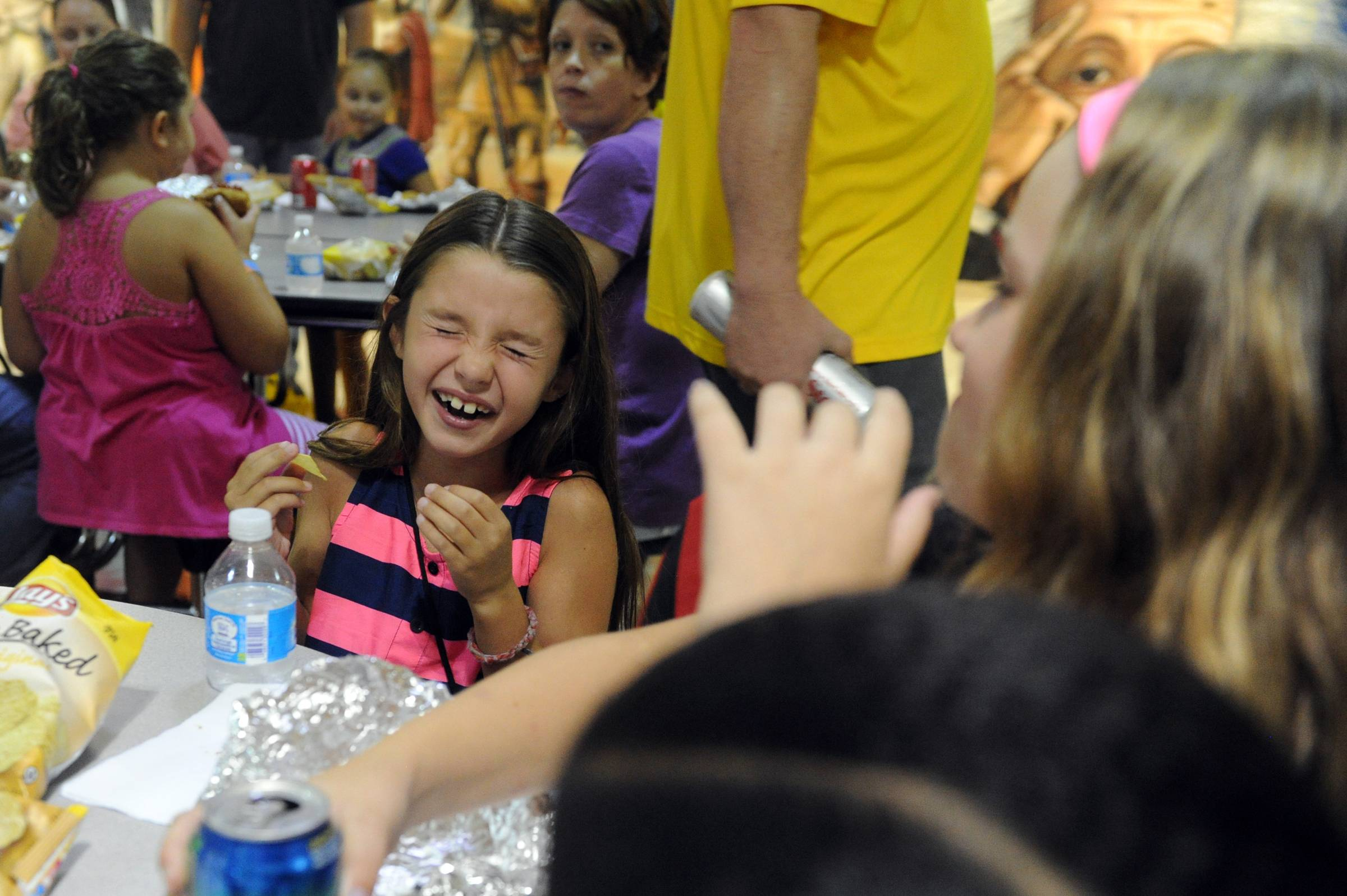 Fourth-grader Avery Stephens, 9, center, laughs as she eats with her friends, Alexa Cecil, 10, right, at the Sharon Elementary School's back to school picnic in Newburgh, Ind.