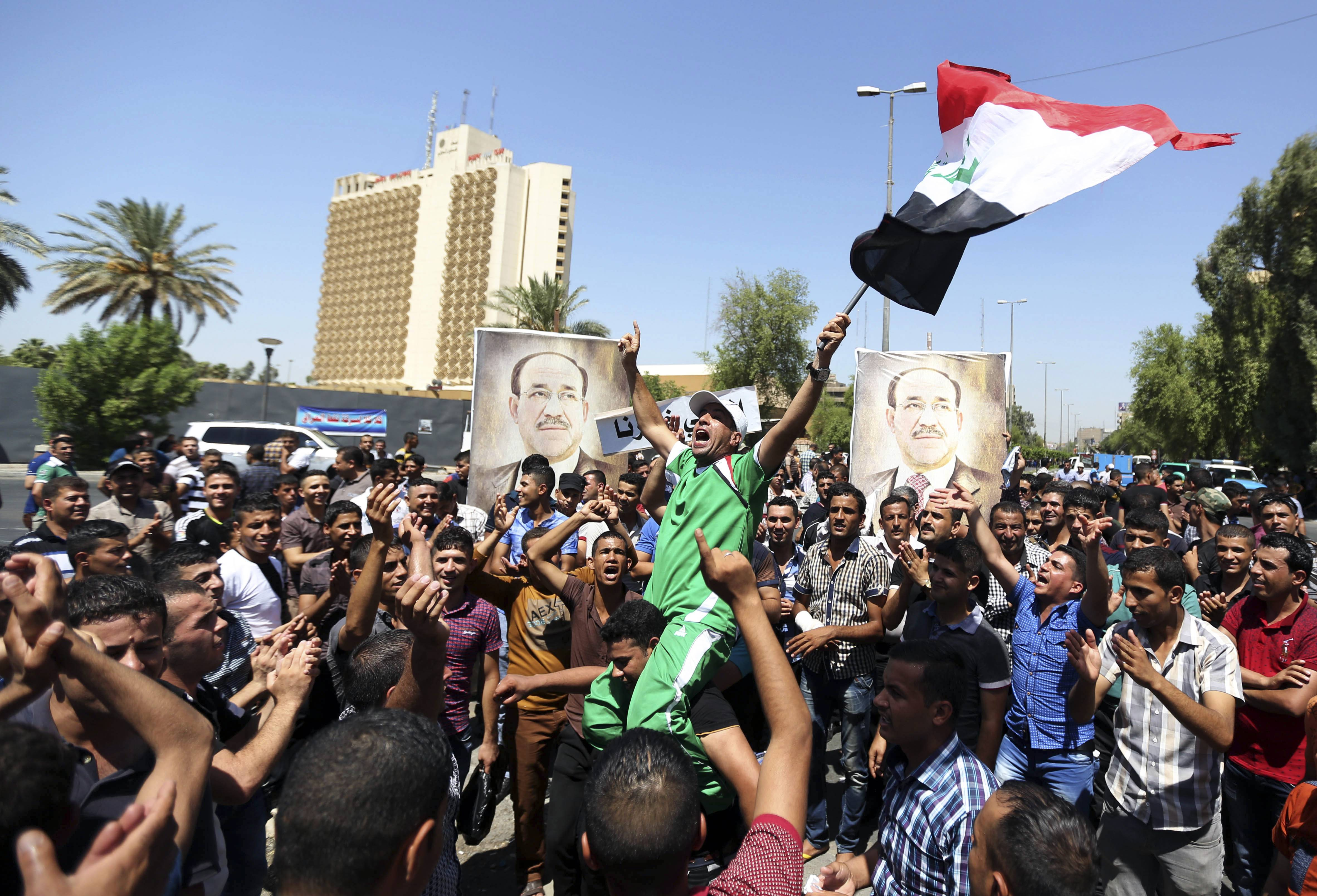 Iraqis chant pro-government slogans and wave national flags in a show of support for embattled Prime Minister Nouri al-Maliki during a demonstration in Baghdad, Iraq, Monday.