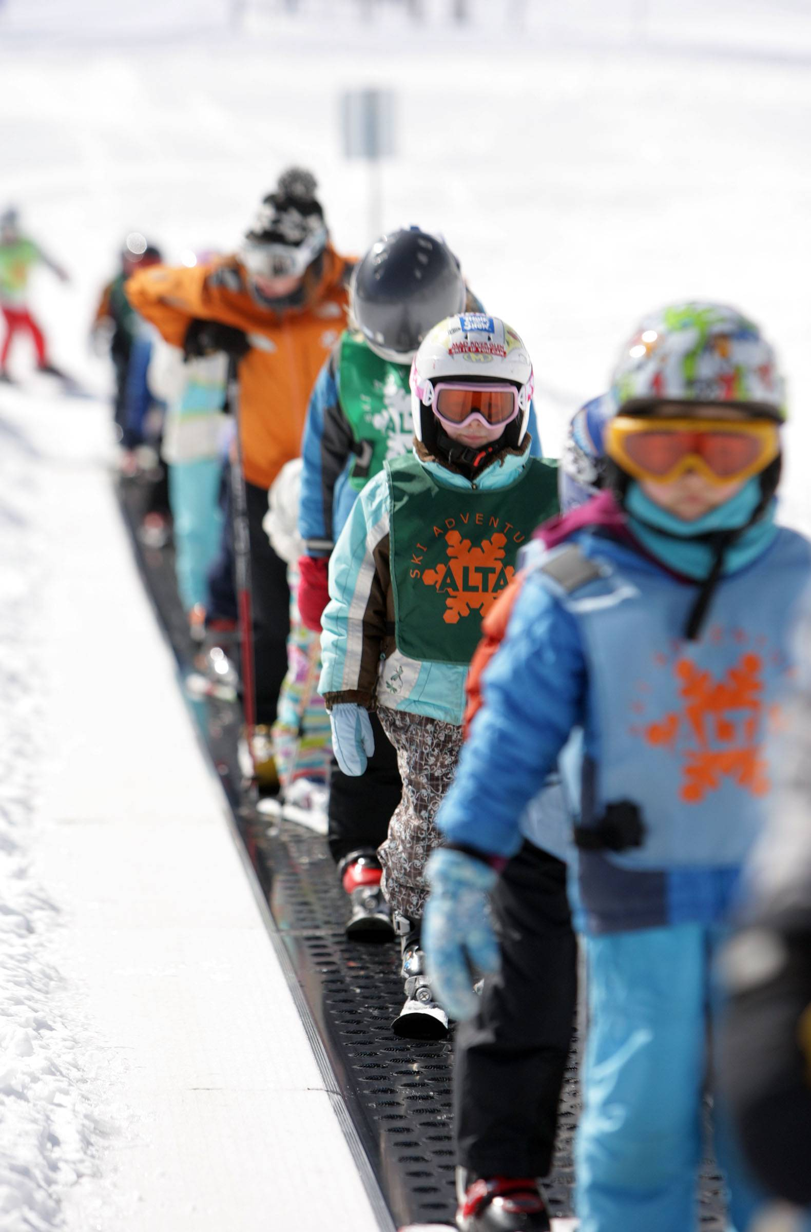 Young skiers ride the conveyor belt on Little Grizz at Alta Ski Resort in Little Cottonwood Canyon near Salt Lake City. A group of snowboarders suing to get access to Alta ski area are headed to court.