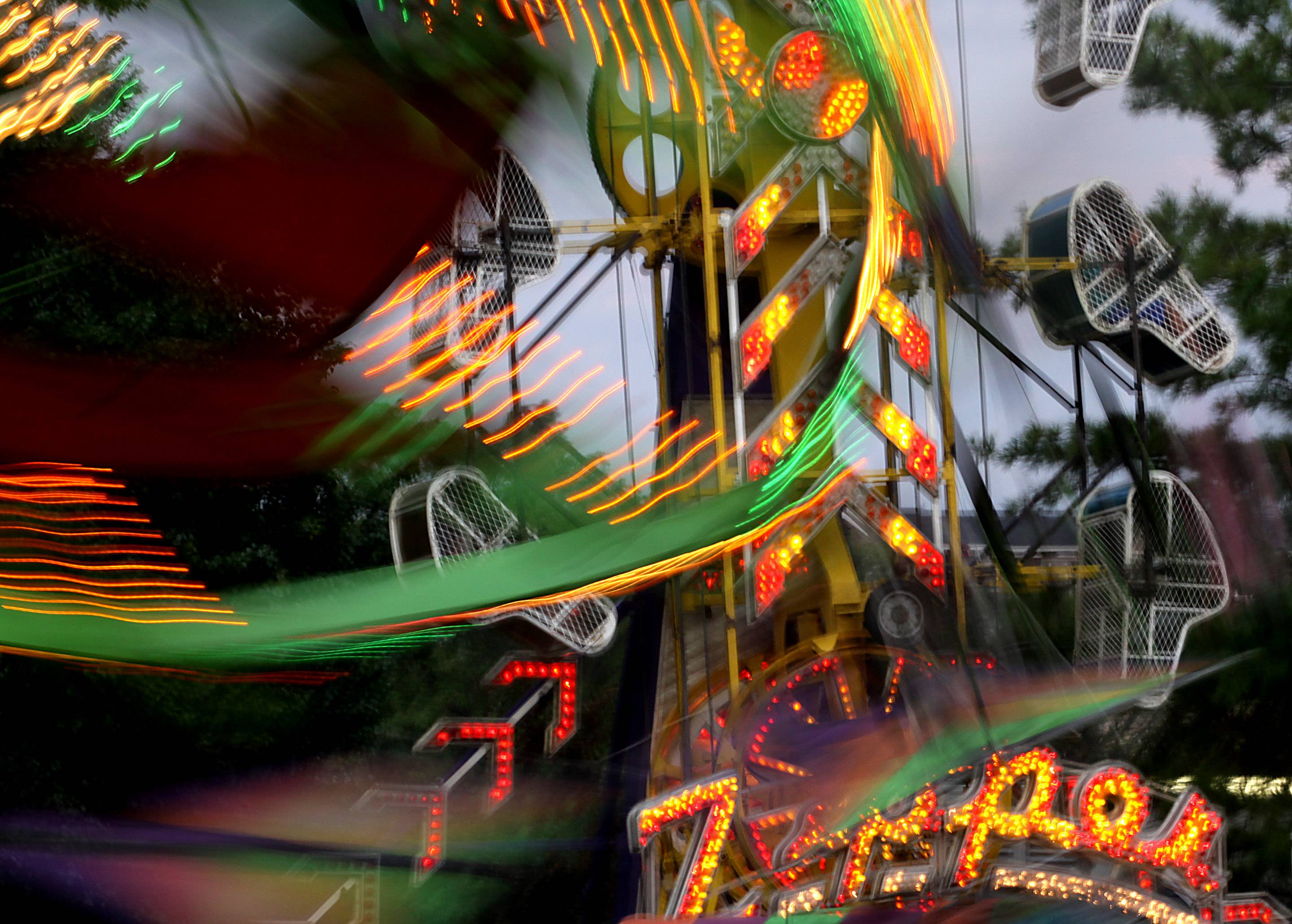 The Zipper amusement ride and others go into motion during South Elgin Riverfest Express at Panton Mill Park.