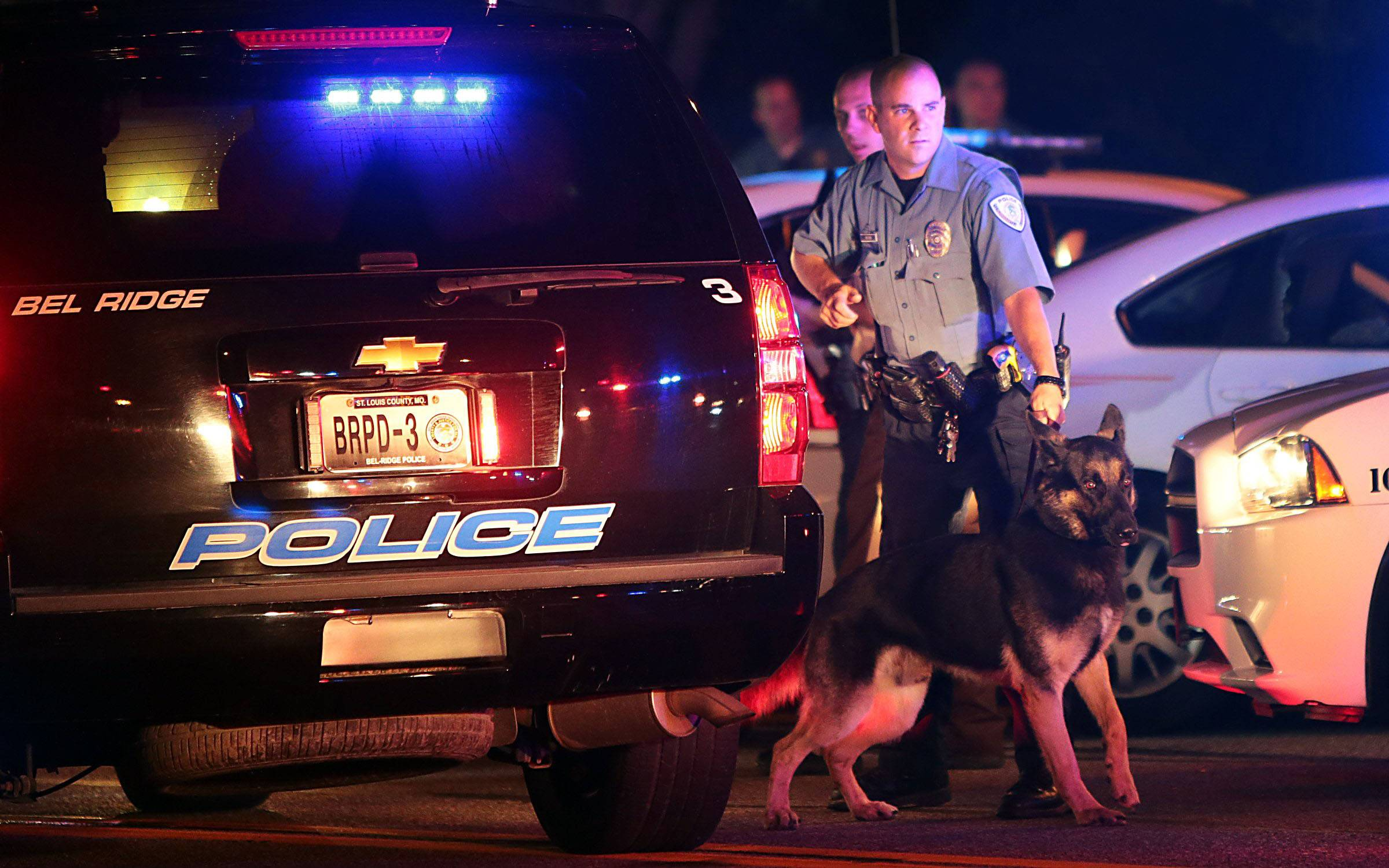 Police officers patrol the area Sunday in Ferguson, Mo.