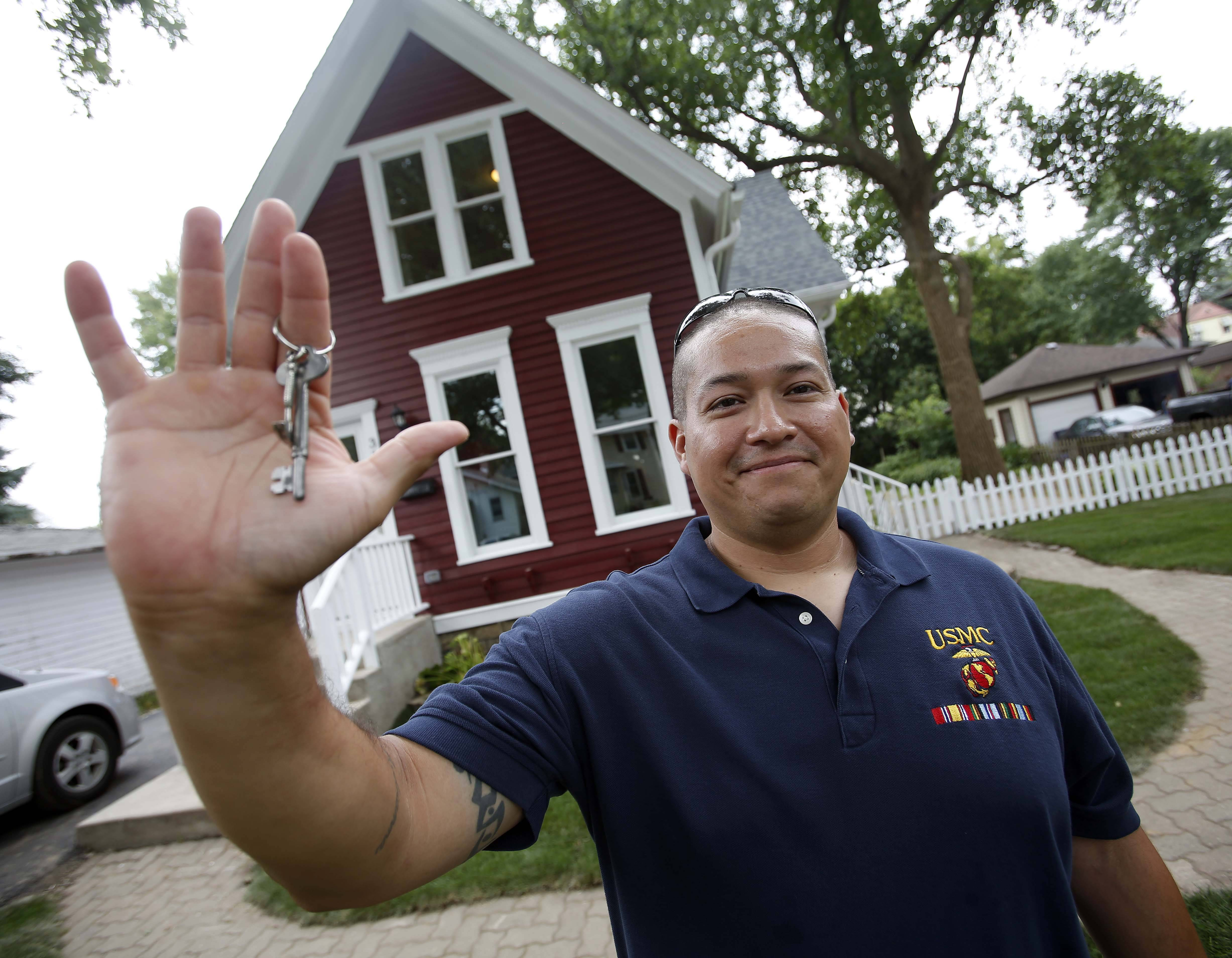 Roberto Cintora, a Marine Corps veteran who grew up in Elgin, proudly holds up his new keys outside his home Sunday. The Elgin native and his twin sons moved into the home Sunday after working with Habitat for Humanity of Northern Fox Valley to rehab it.