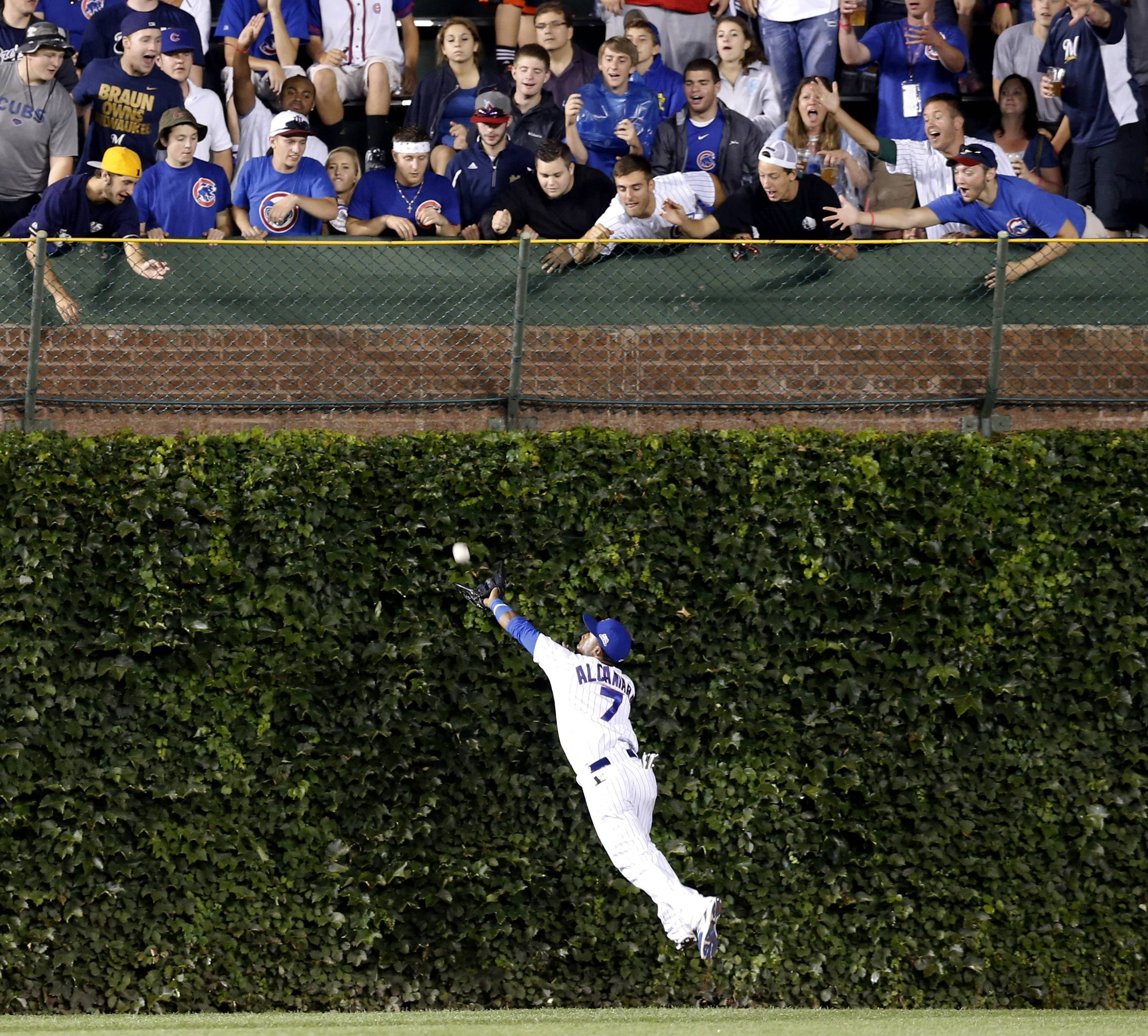 Chicago Cubs center fielder Arismendy Alcantara is unable to catch a fly ball by Milwaukee Brewers' Scooter Gennett, during the seventh inning of a baseball game Monday in Chicago. Alcantara recovered relaying to Starlin Castro who threw out Ryan Braun at home.