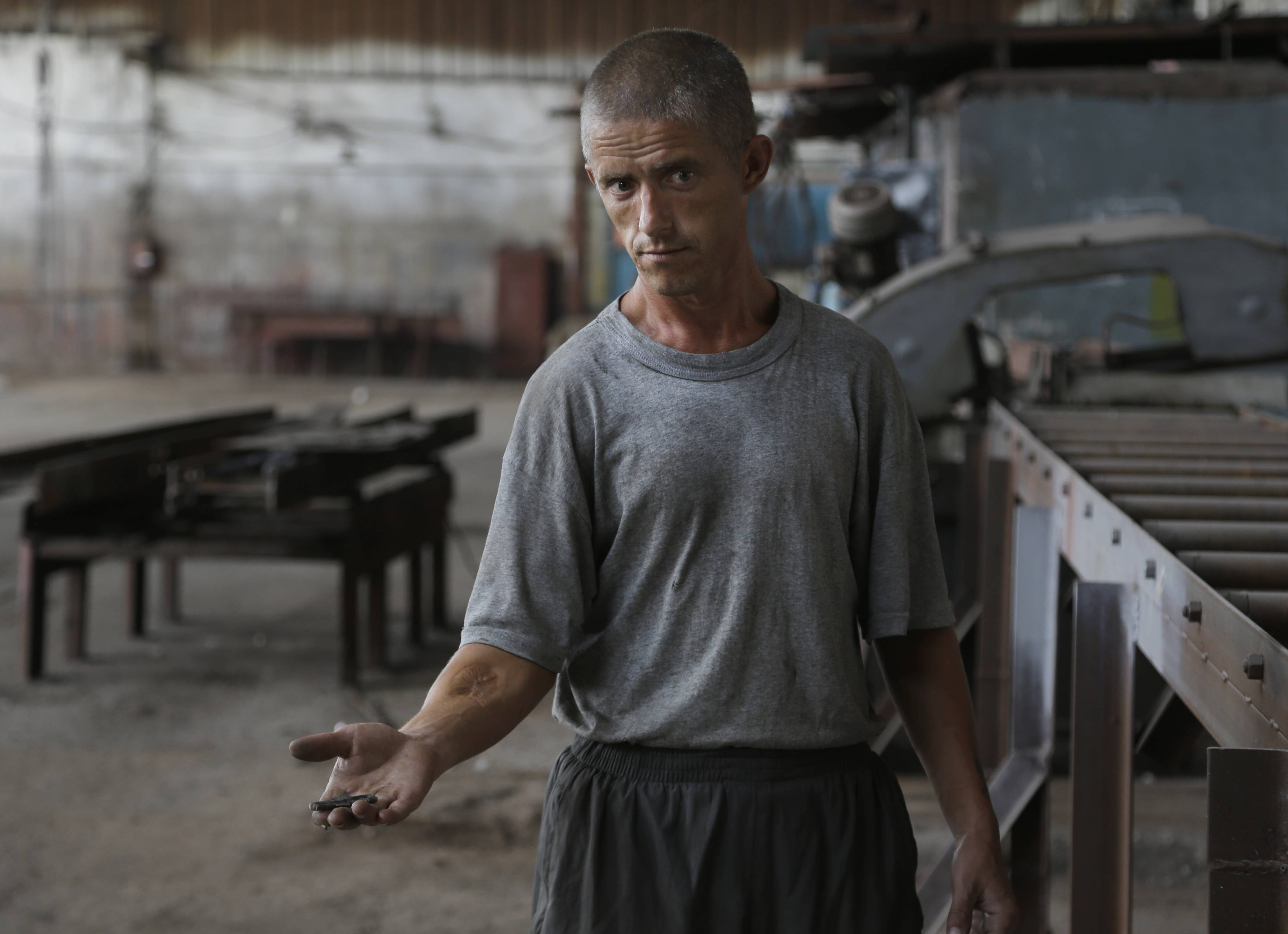 A prisoner displays fragments of a shell after shelling in Donetsk, eastern Ukraine, Monday.