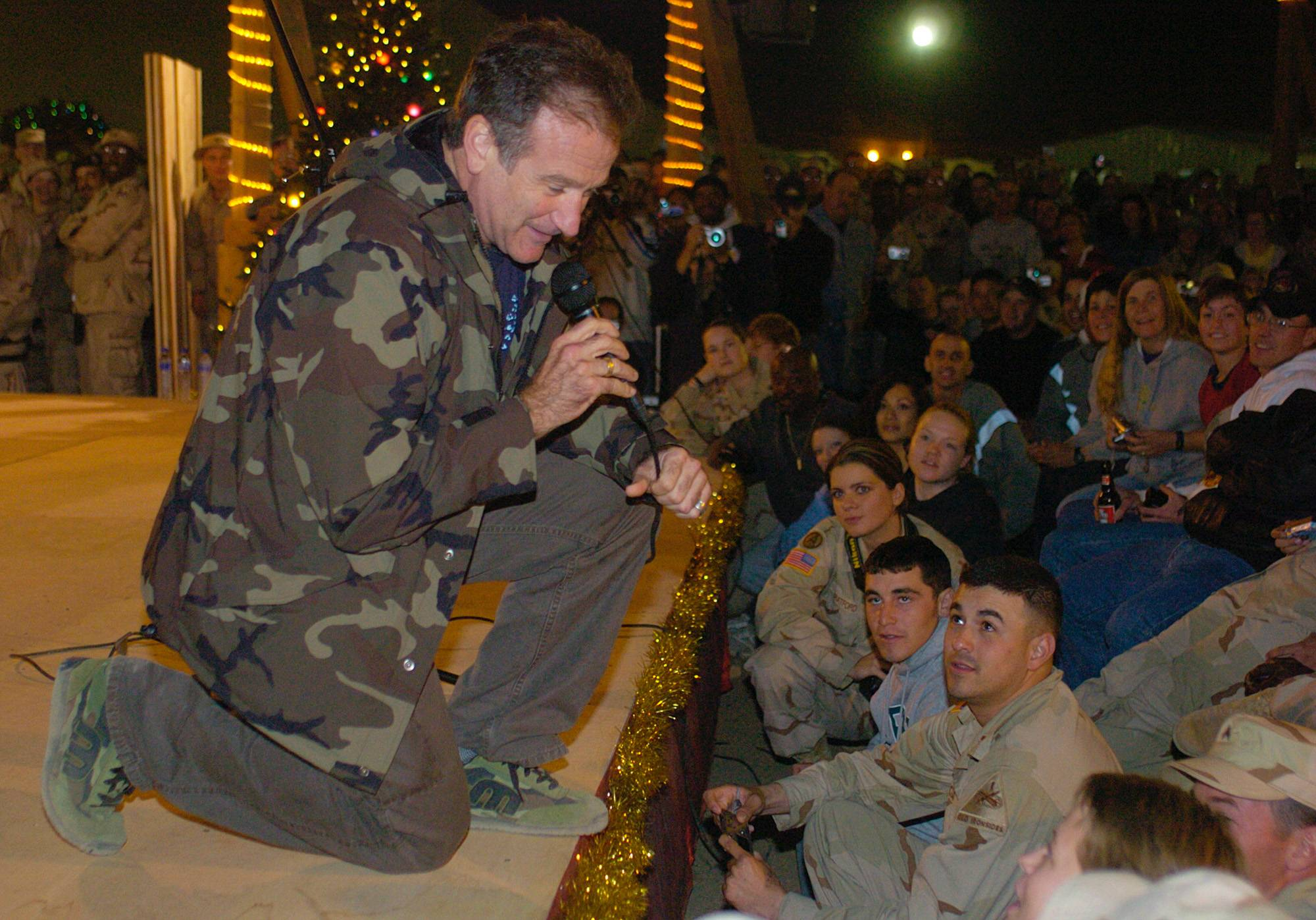 Comedian Robin Williams, wearing a camoflague jacket, kneels as he entertains a crowd Monday, Dec, 15, 2003 of U.S. Army troops as part of a United Services Organiztion Holiday Tour, Monday, Dec, 15, 2003 at Camp Arifjan, Kuwait.