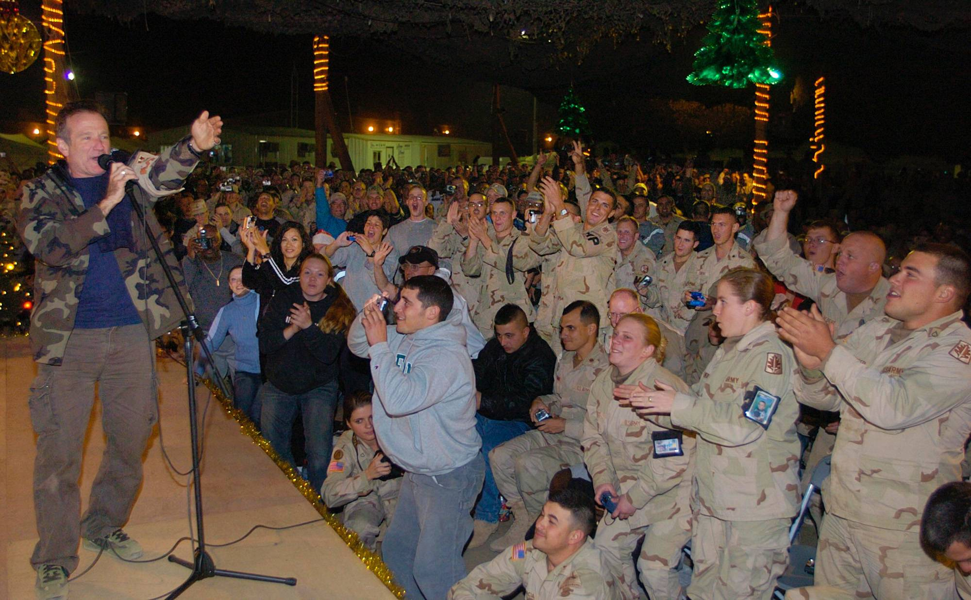 Comedian Robin Williams, wearing a camouflage jacket, entertains a cheering crowd of U.S. Army troops as part of a United Services Organiztion Holiday Tour, Monday, Dec. 15, 2003 at Camp Arifjan, Kuwait.