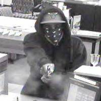 The smoke from a gun being fired at a bank teller in Bolingbrook Monday afternoon can be seen in this surveillance photo released by the FBI.